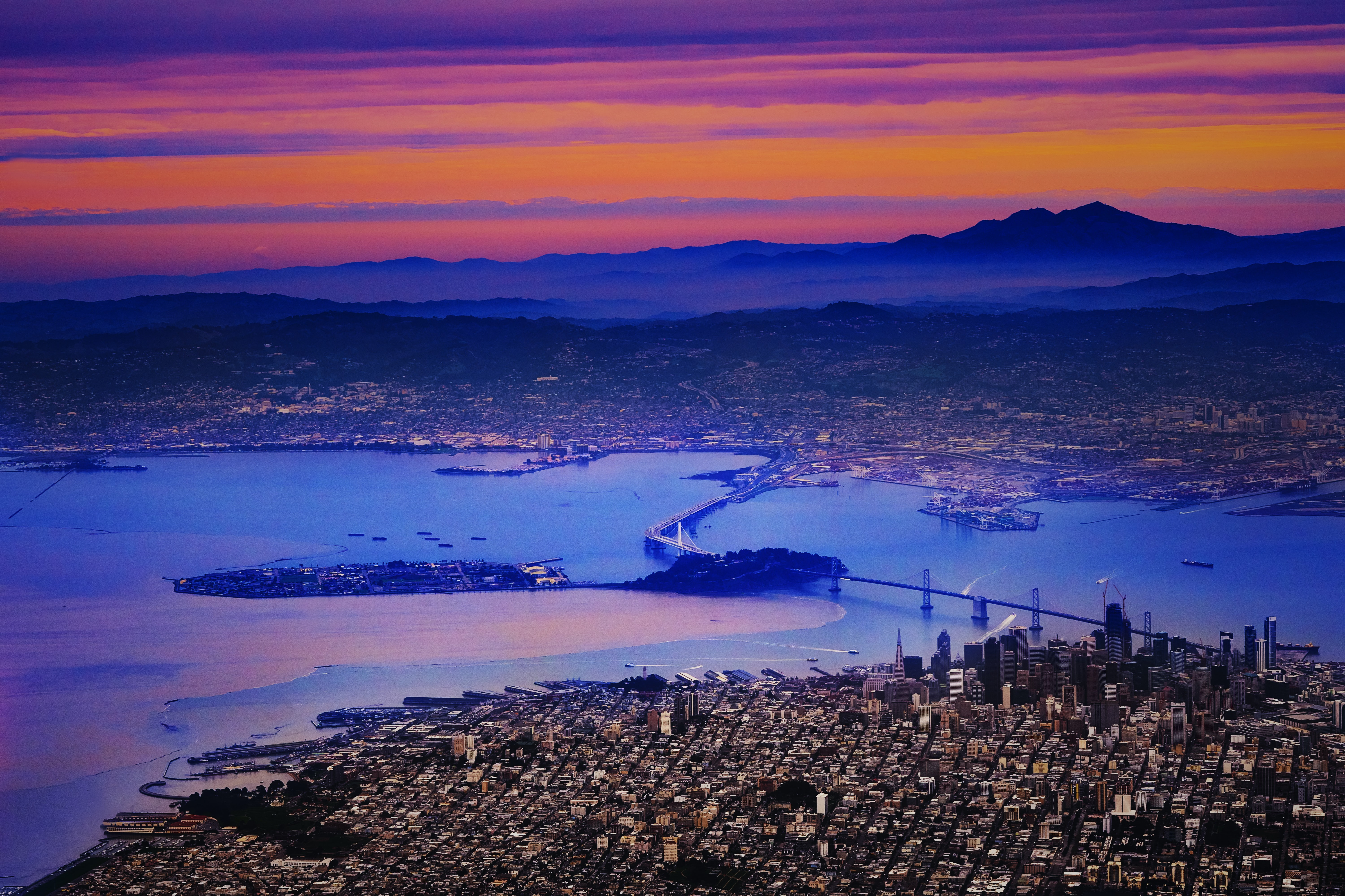 Sunset over San Francisco with a bridge in the foreground spreading over the water