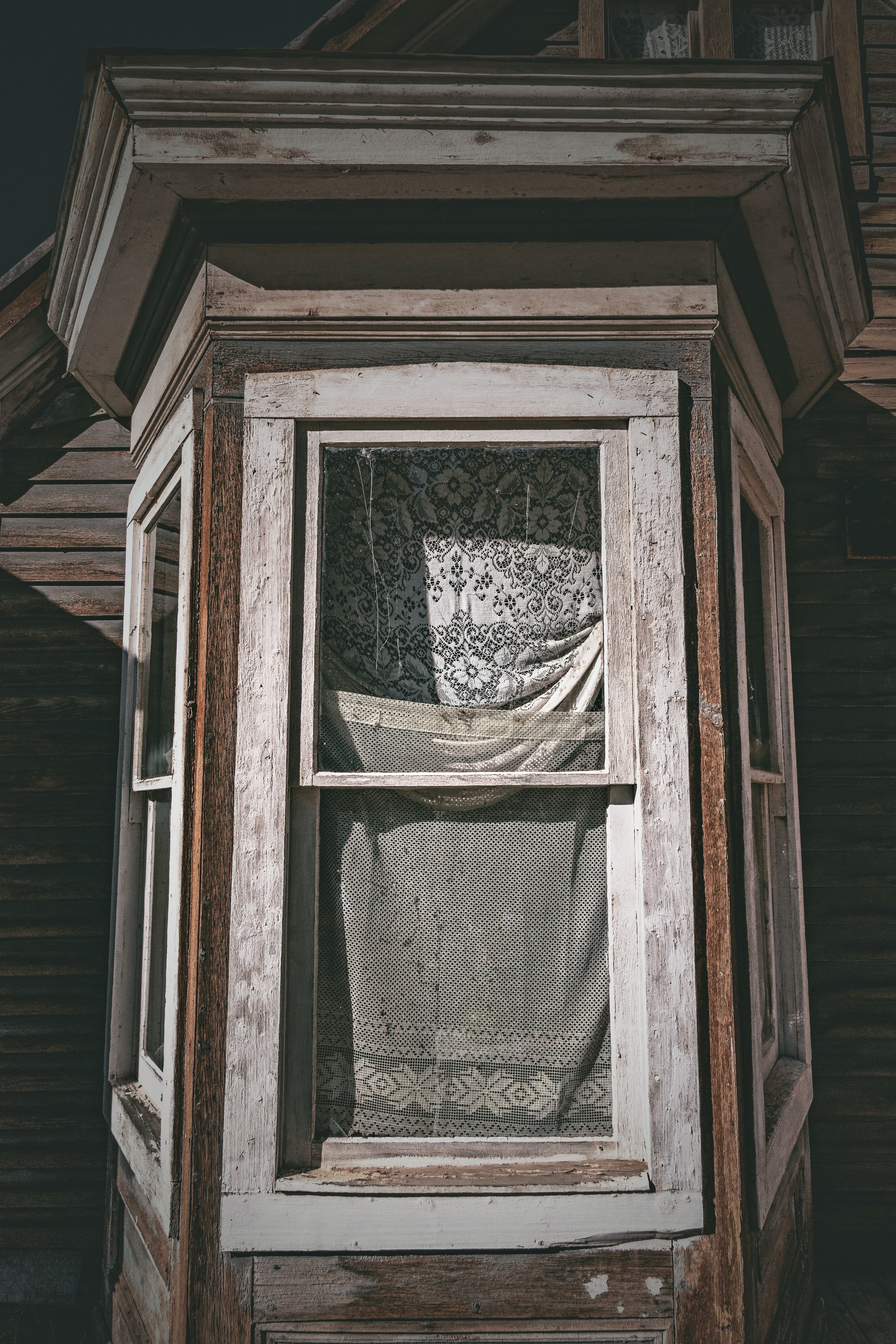 The facade of an old house with cracked framing and window curtains made of used sheets.
