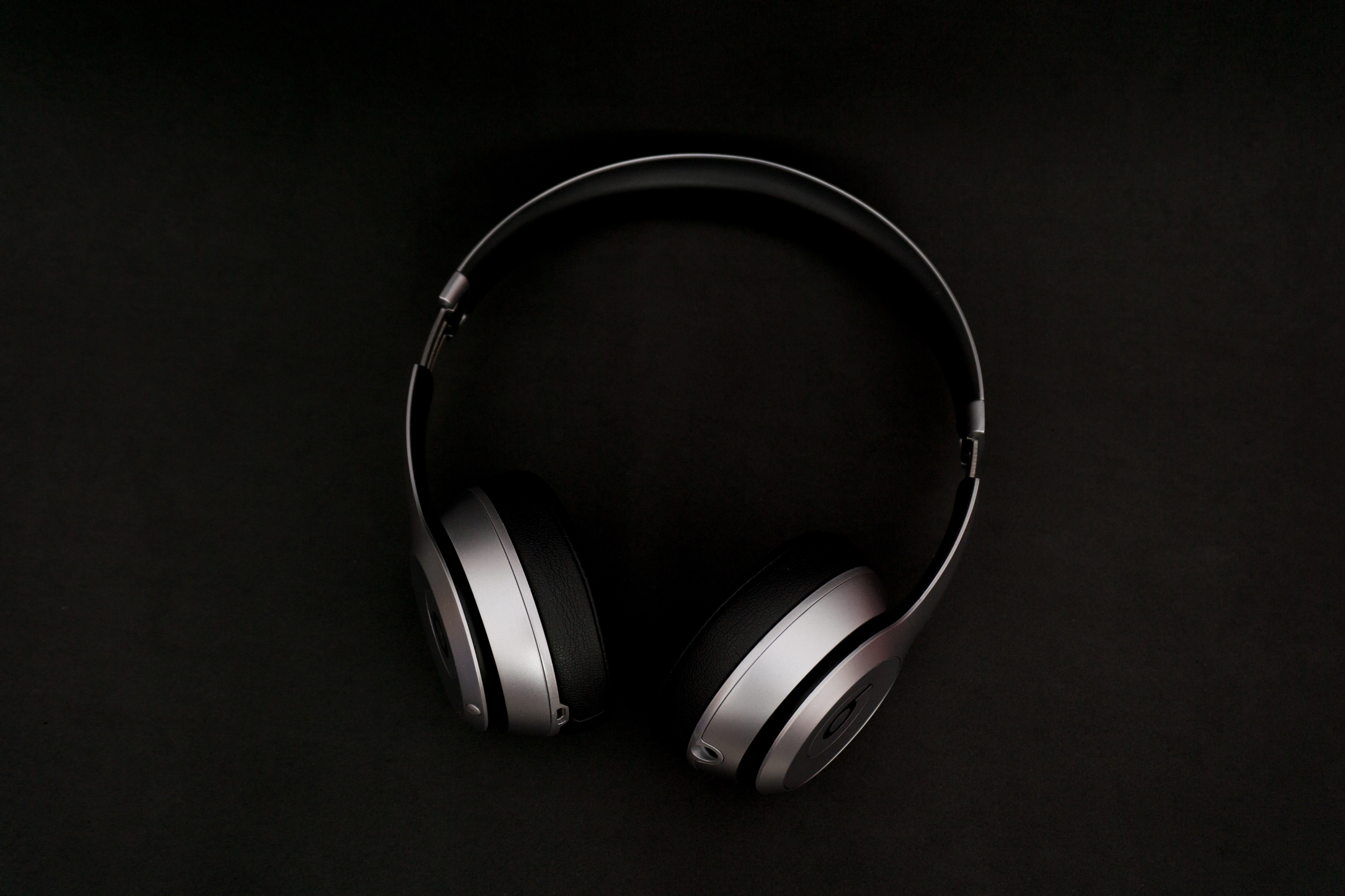 Silver and black earphones in black background standing upright