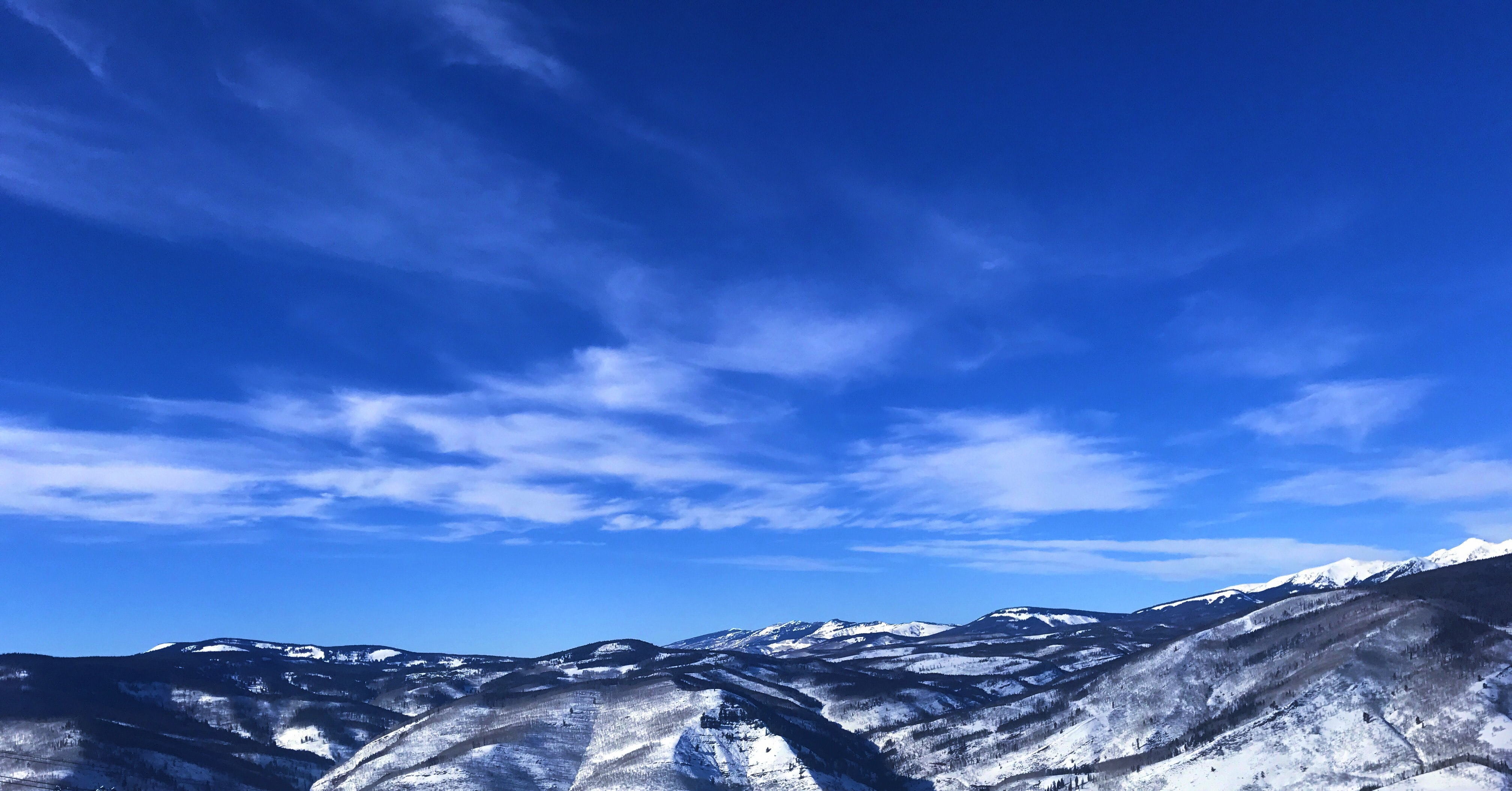 A low snow-capped mountain range under a blue sky