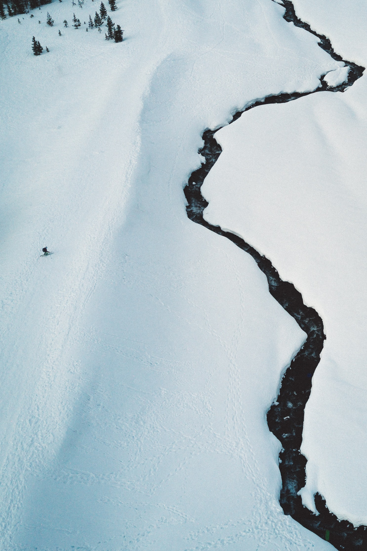 A drone shot of a small river flowing through snowy plains