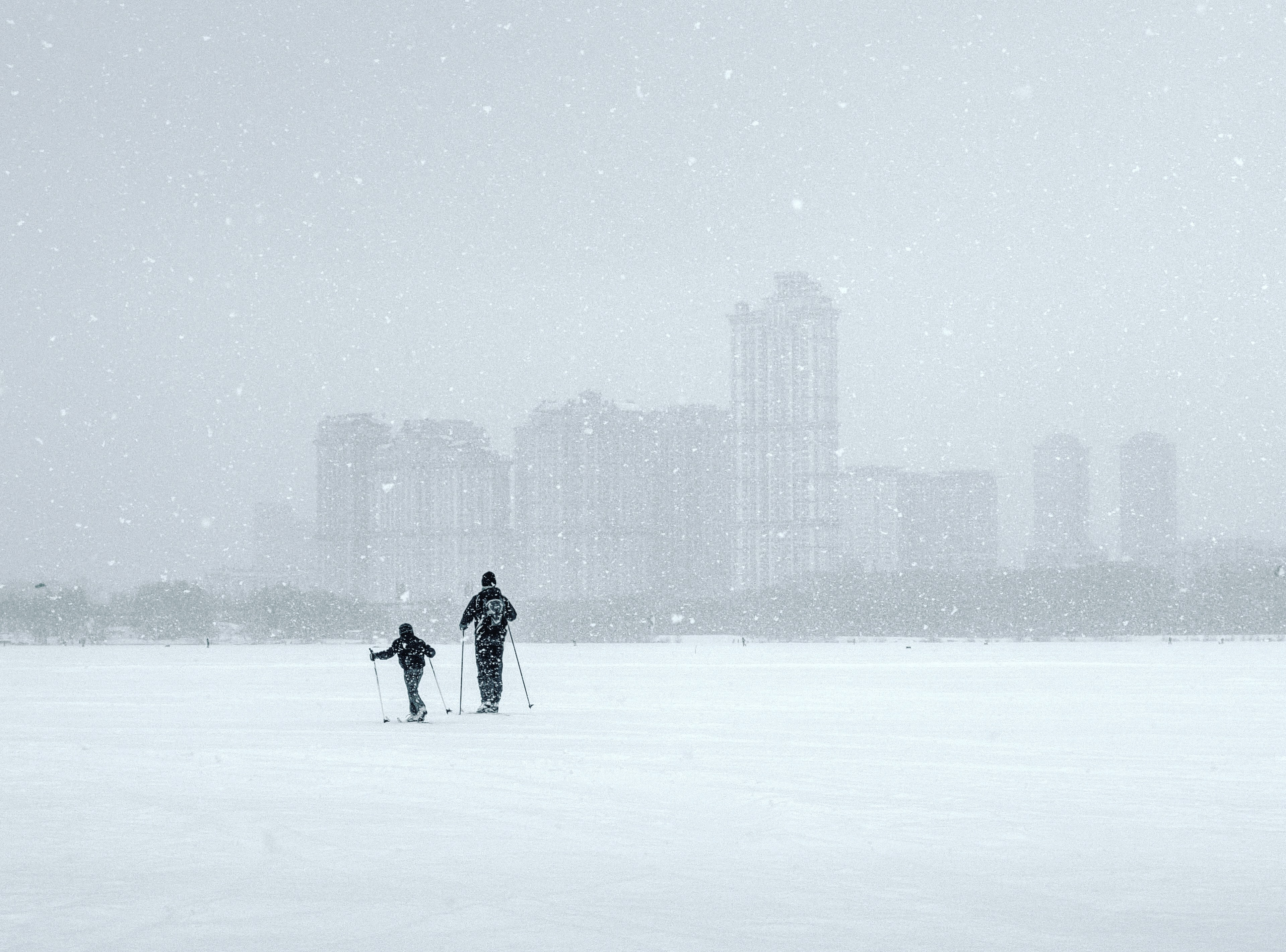 Adult and child in snow on skis near city skyline