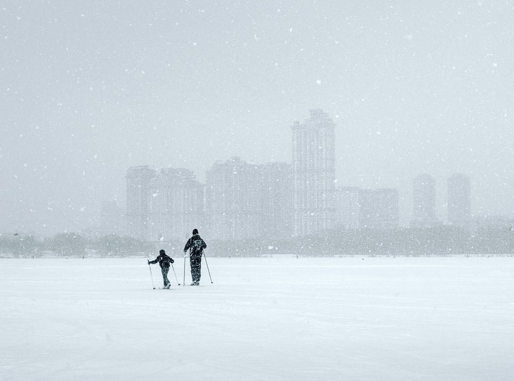 two persons walking on snow