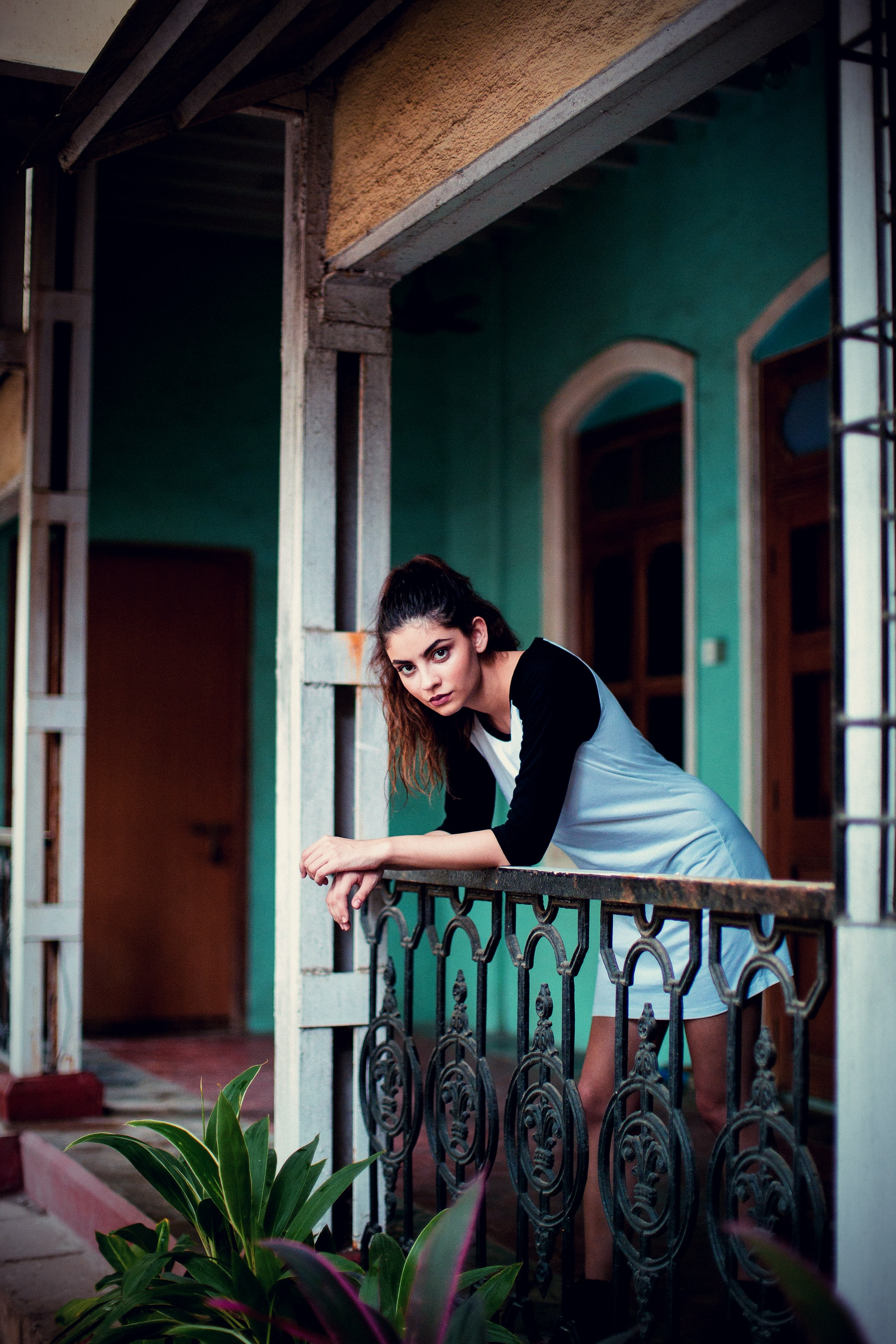 A brunette girl leaning over her balcony and staring at the camera