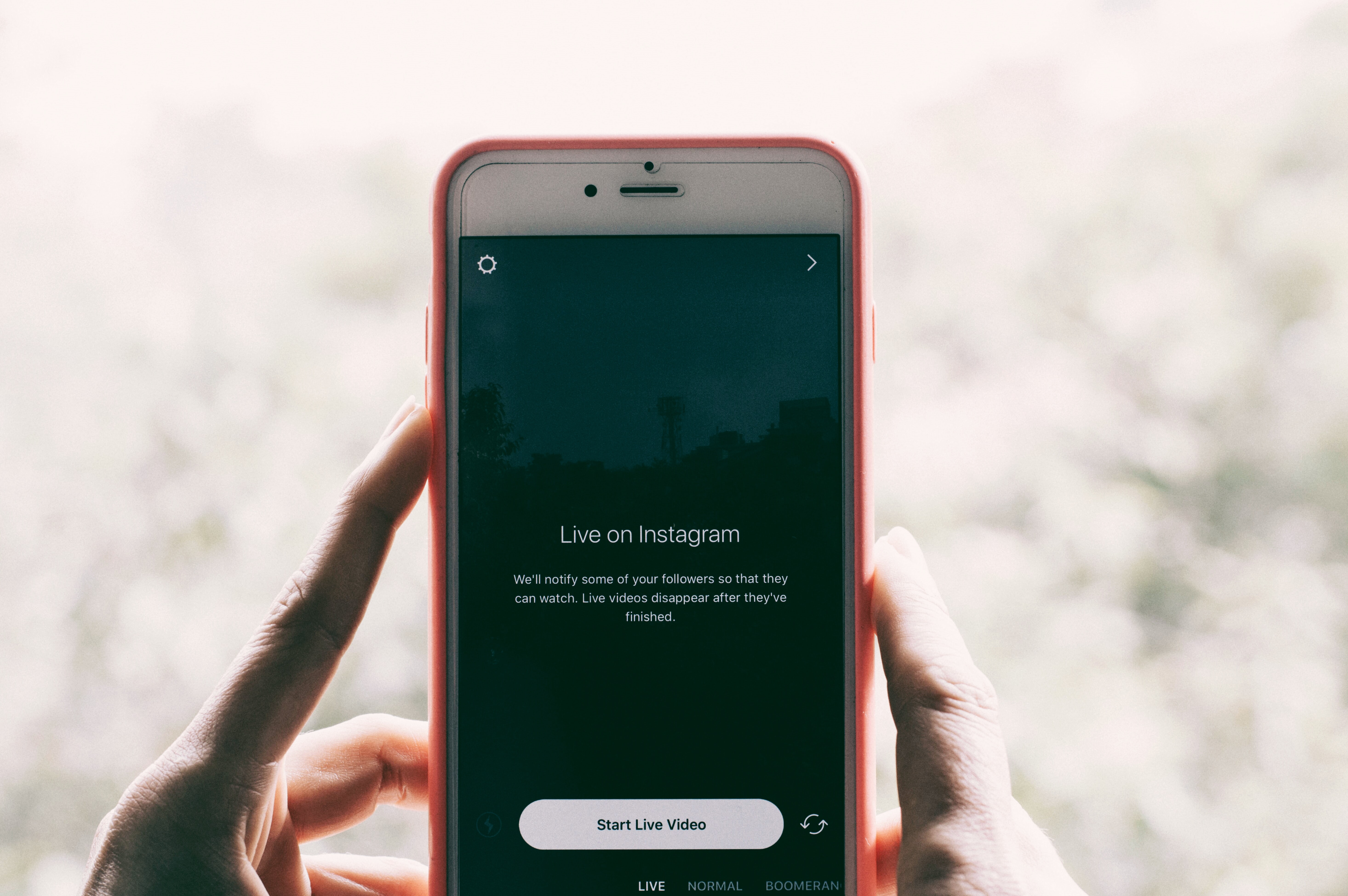 A person holding an iPhone with Instagram live videos open