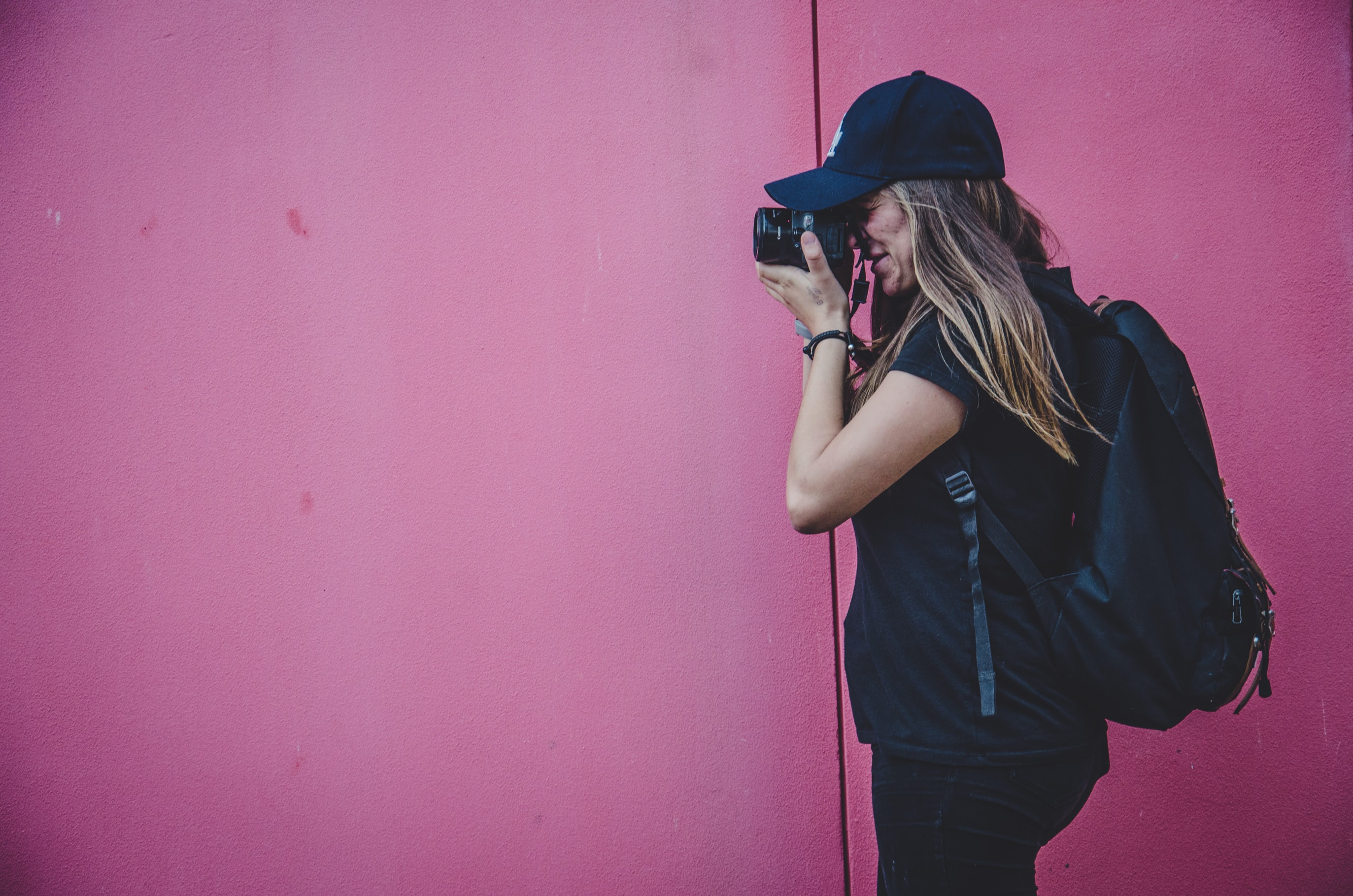 A woman wearing a black hat and backpack holding a camera taking a photo in Surry HIlls