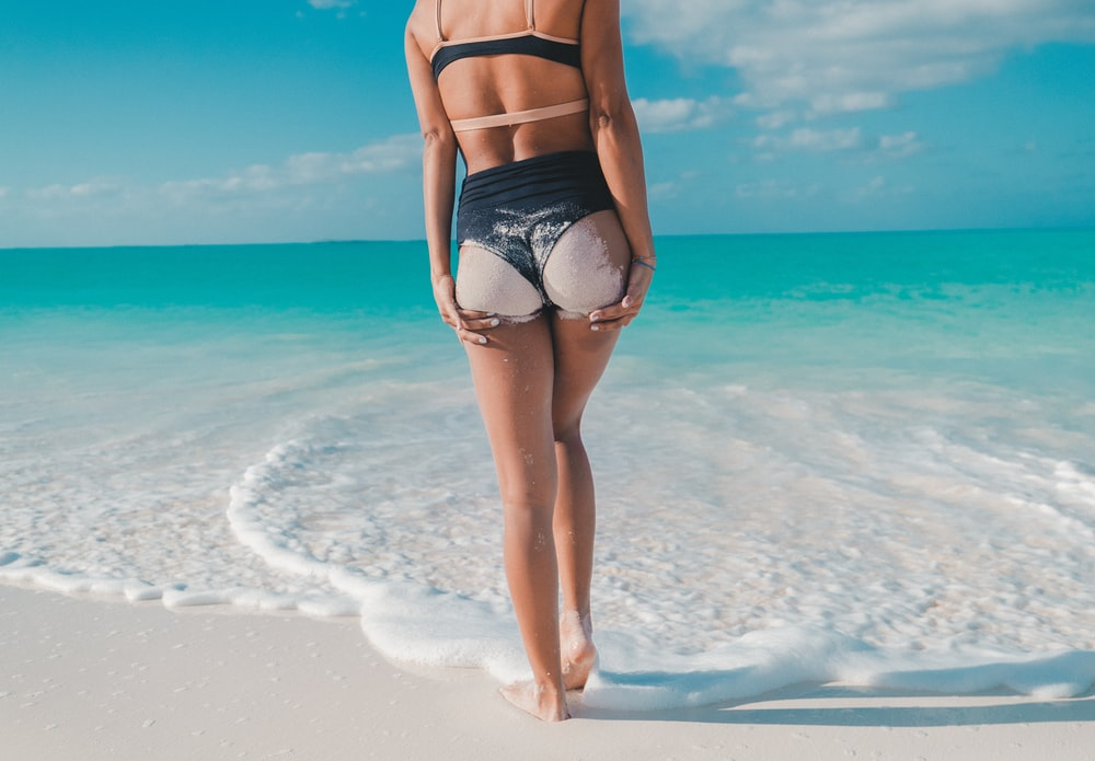 back view photography of woman in black bikini walking towards the sea