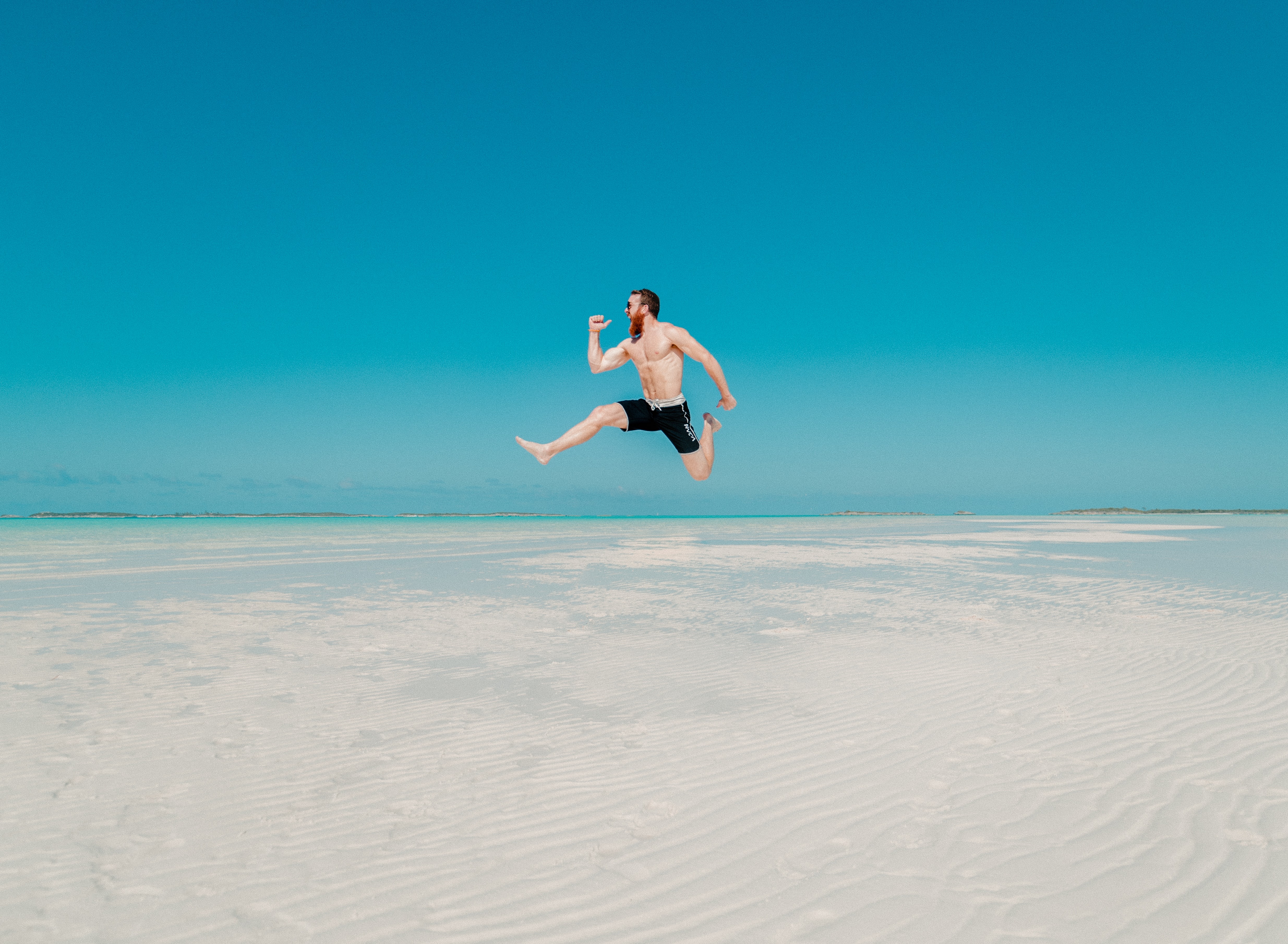 A shirtless muscular man in shorts in the middle of a high jump above a sandy beach