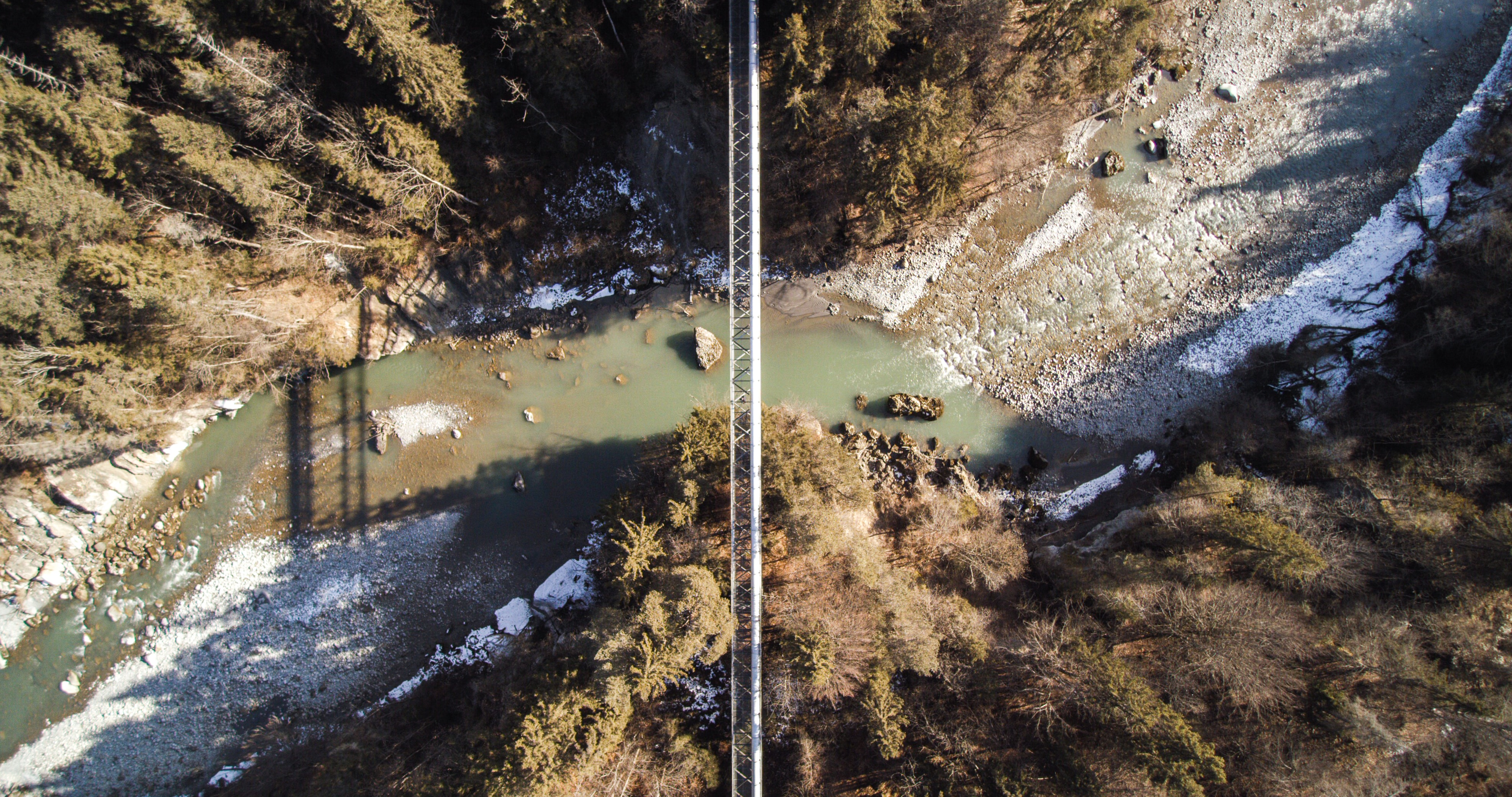 aerial photography of bridge over cliff with body of water at daytime