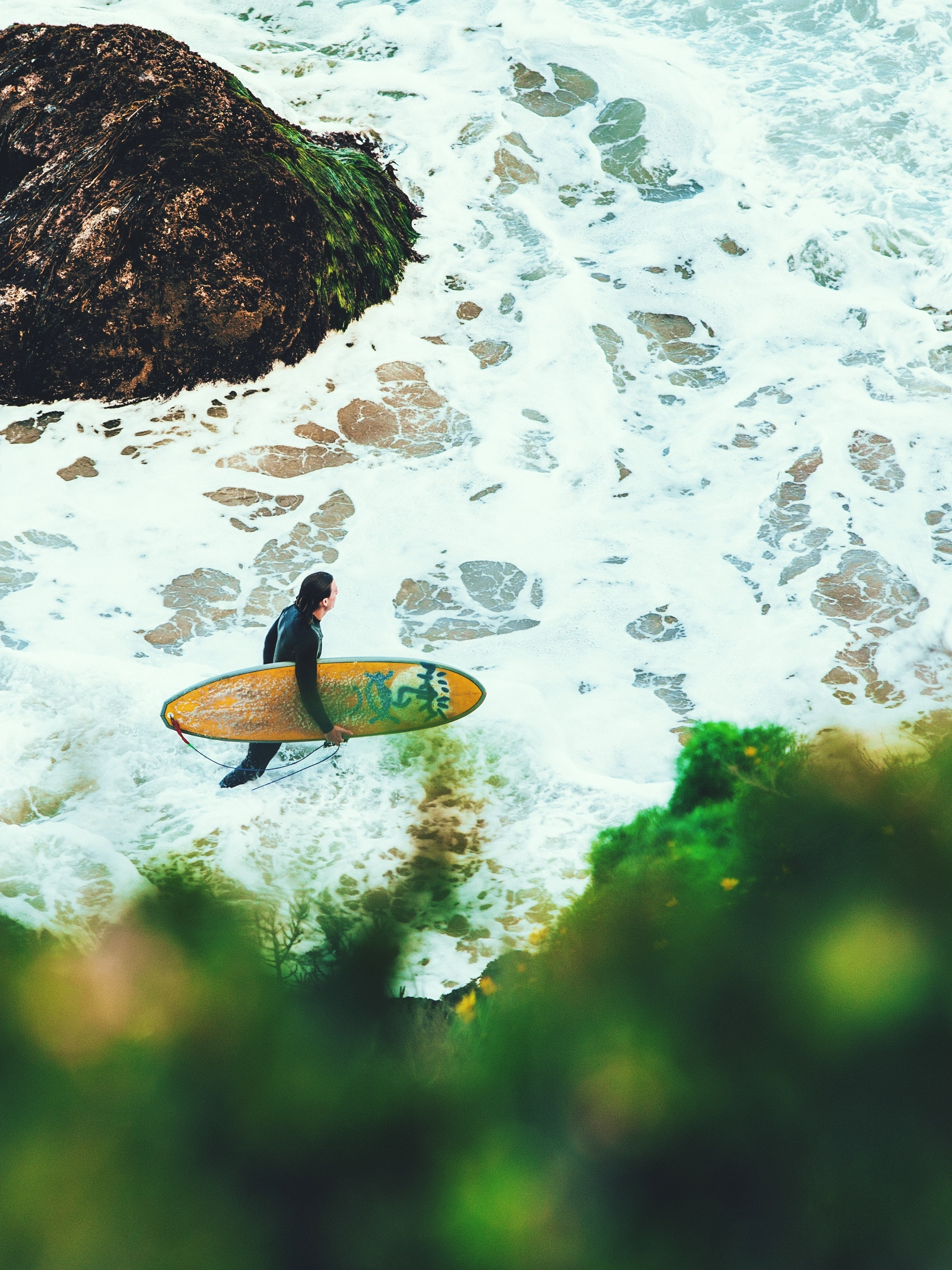 A male surfer in a wetsuit carrying a board into the foaming sea, surrounded by rock formations at Point Dume