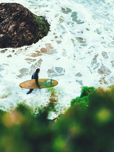 man on beach carrying surfboard