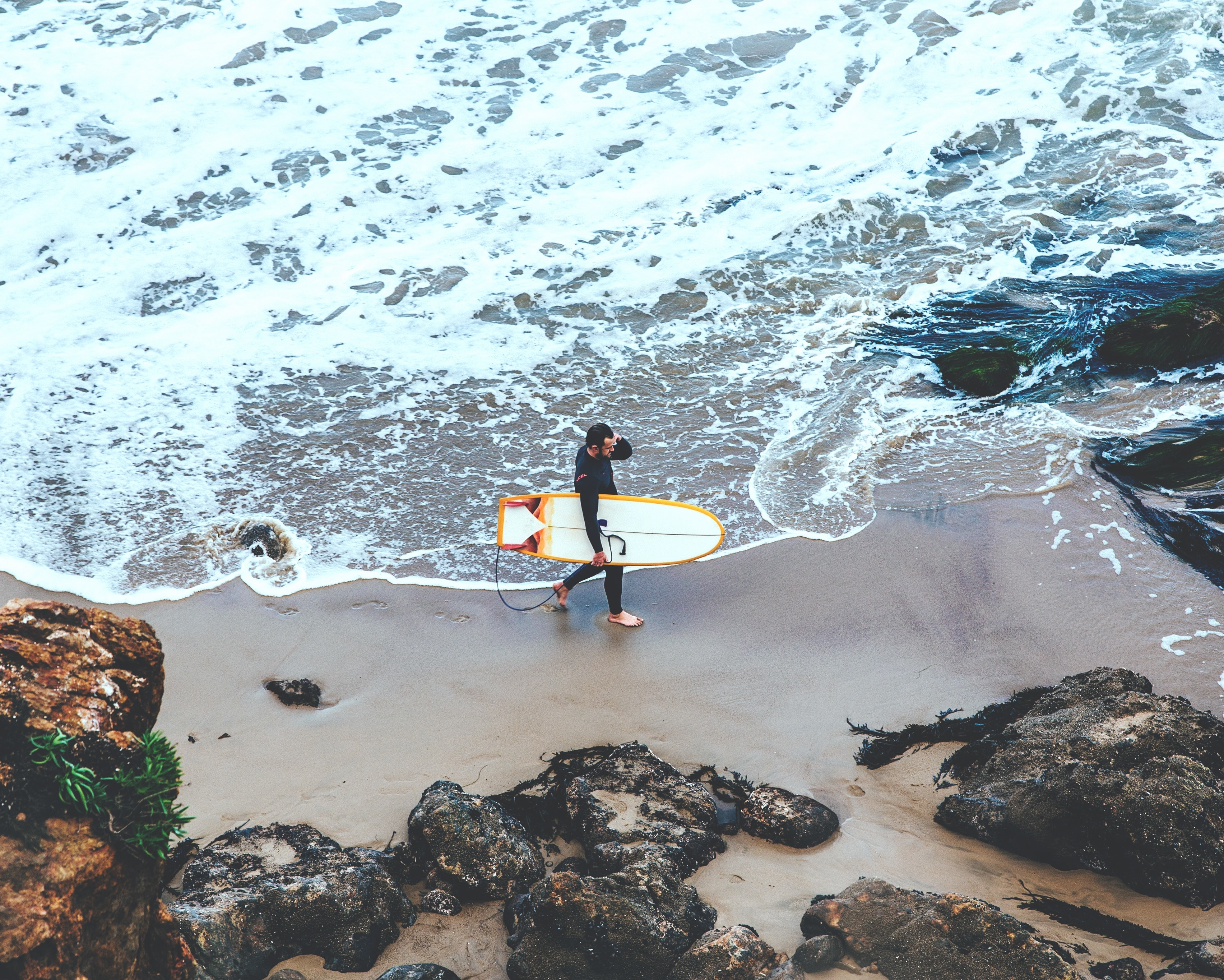 A shot of a surfer carrying a white board along a small bay, taken from above as waves lap the shore at Point Dume