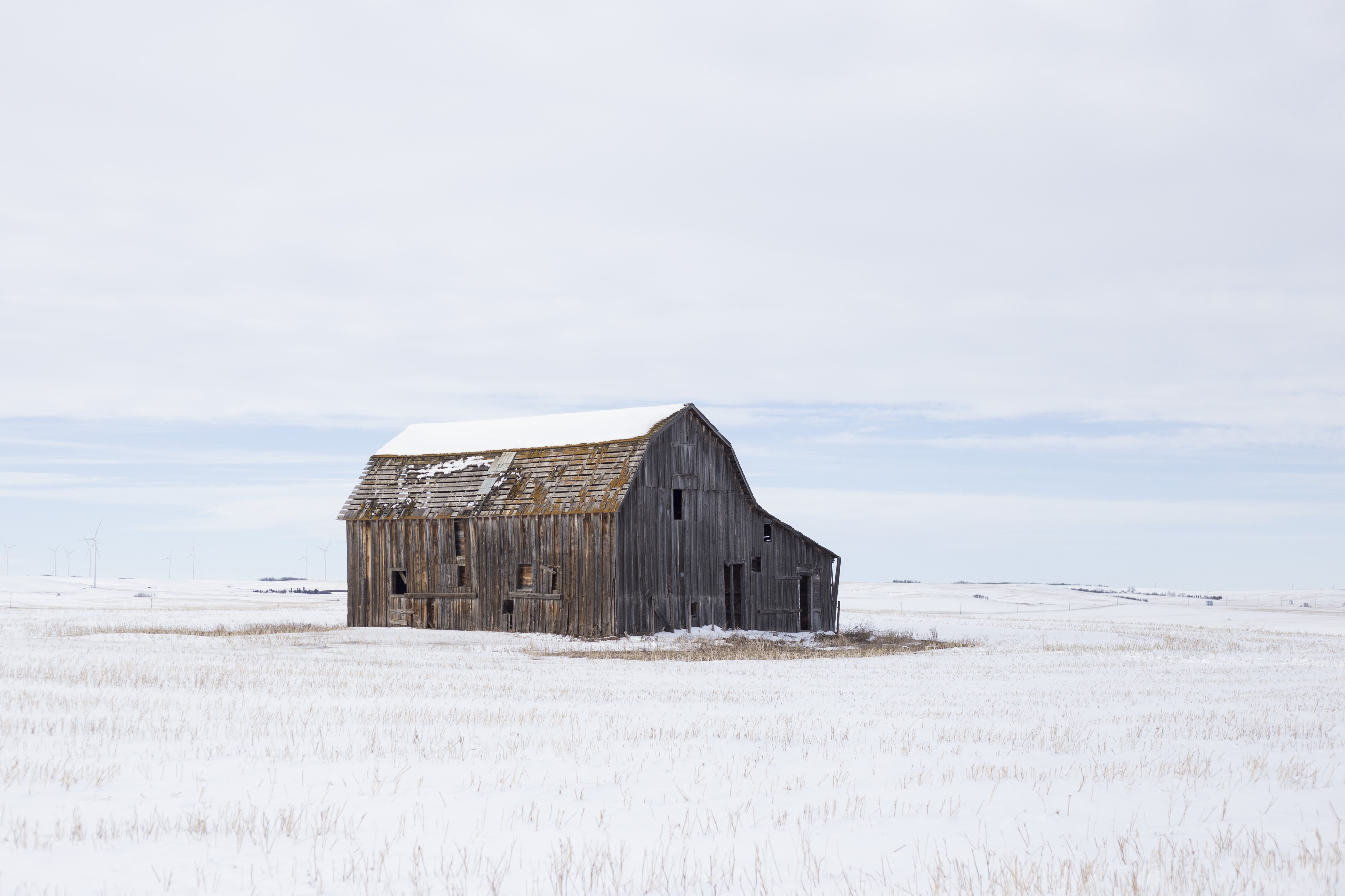 A rustic farm shed sitting in the middle of snow covered farm field under a cloudy sky