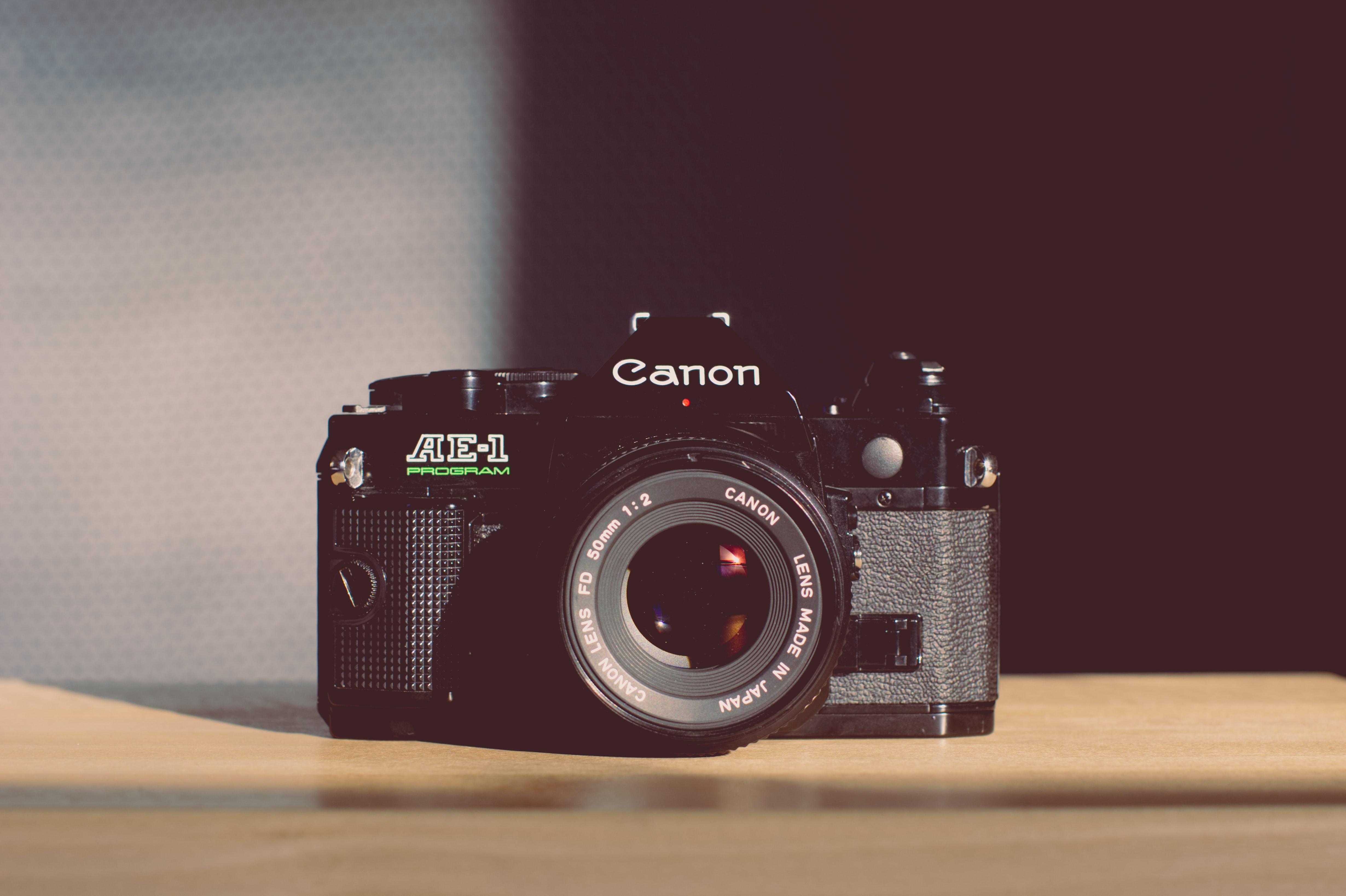 Vintage Canon AE-1 Program with a 50mm lens on a light colored wooden surface beside a partly shadowed wall