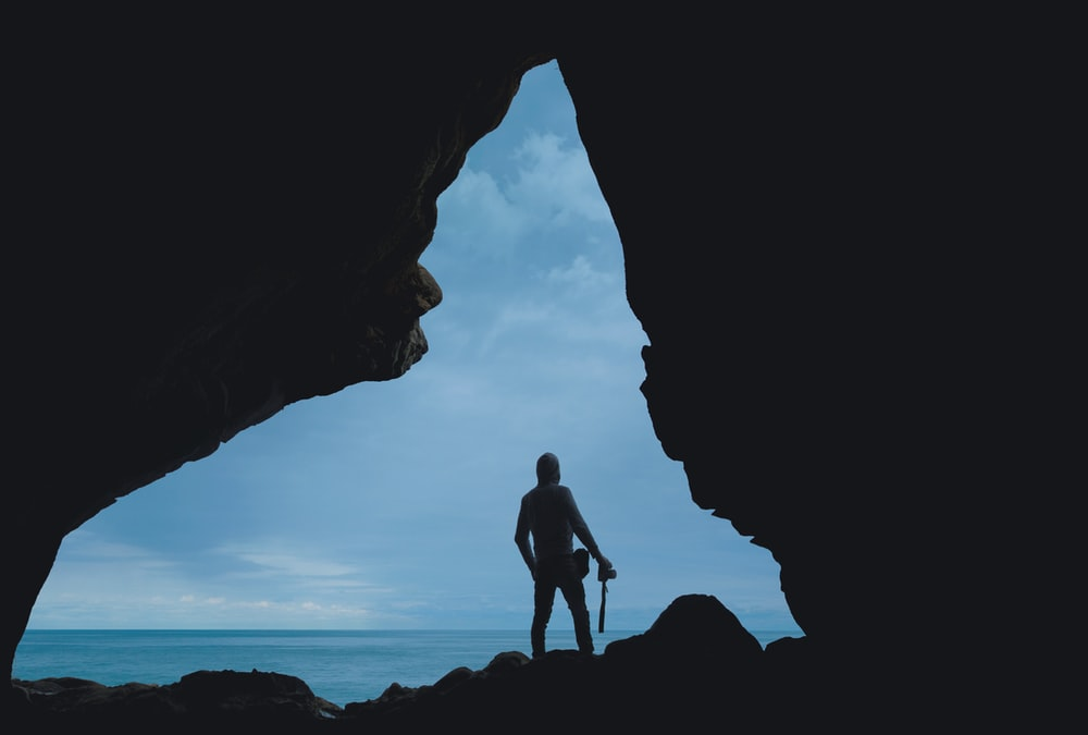 silhouette of person standing on rock