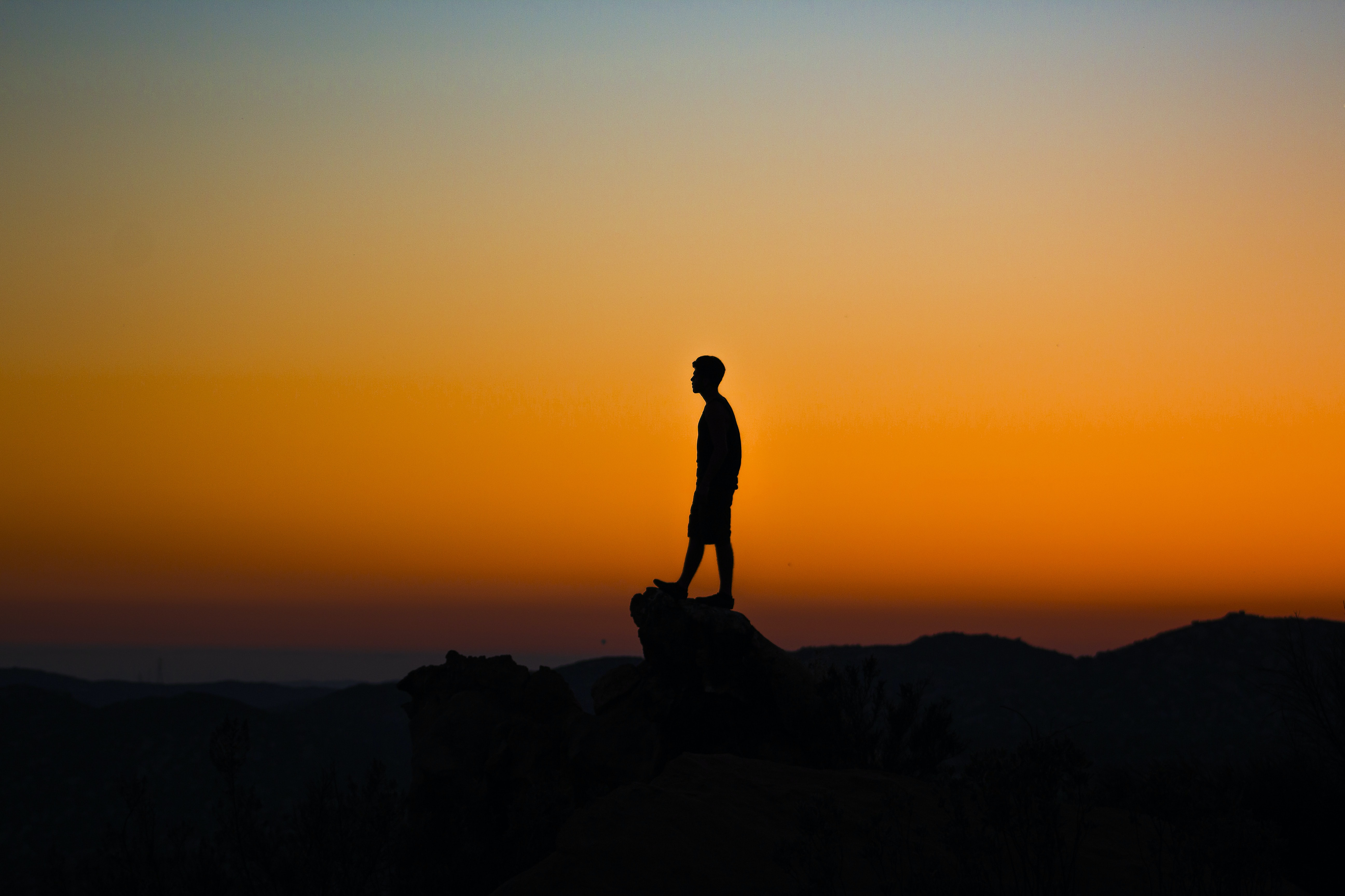 A silhouette of a man standing on a ledge against the backdrop of orange sky at sunset