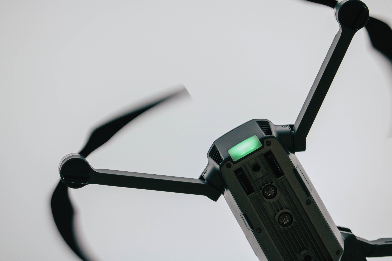 A close-up of a black DJI drone in flight
