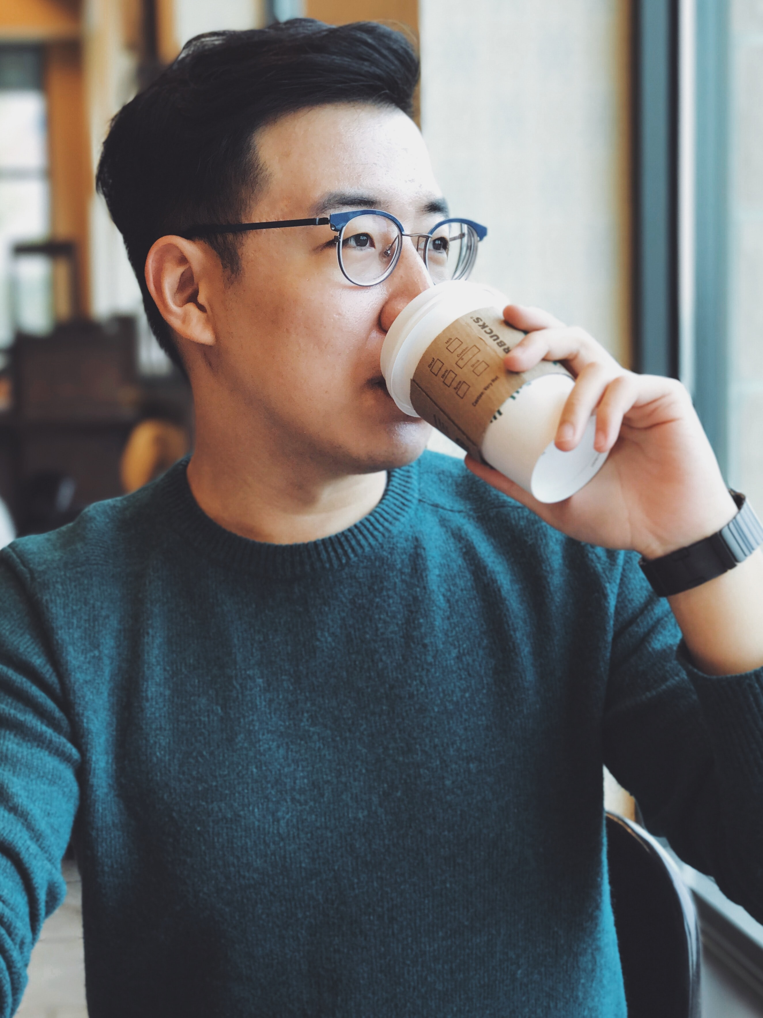 Man in glasses sipping on a cup of starbucks coffee in a cafe