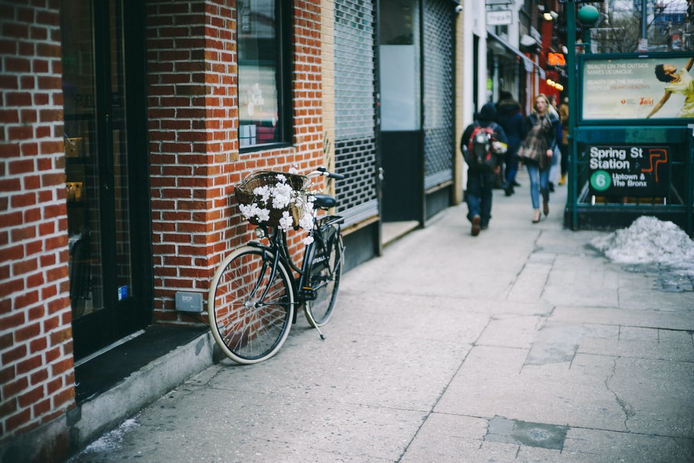 black city bicycle parked beside brown concrete brick wall