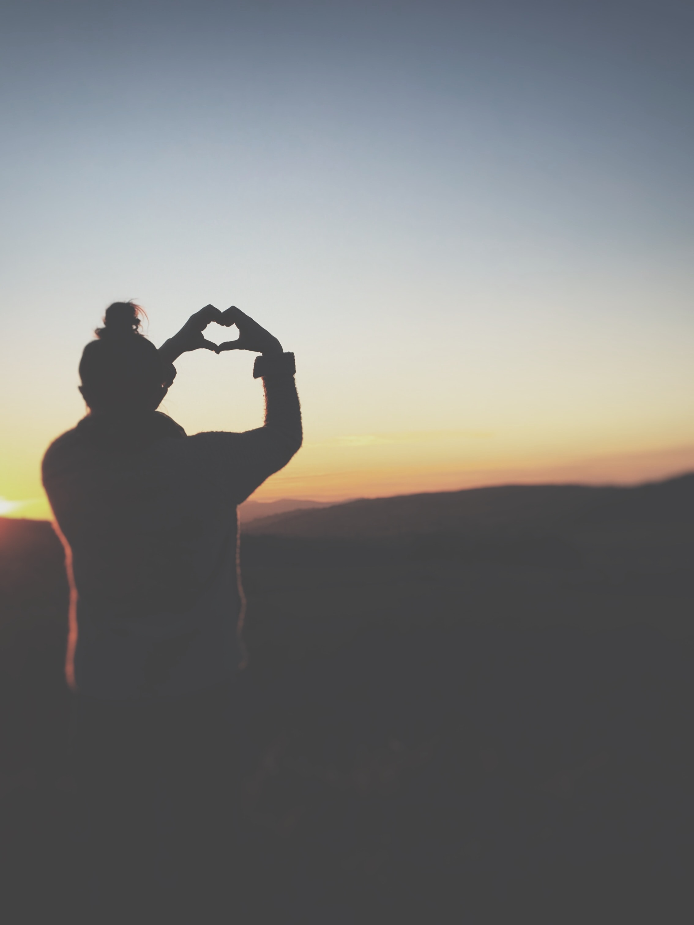 A silhouette of a person making a heart shape with their hands against the twilight sky