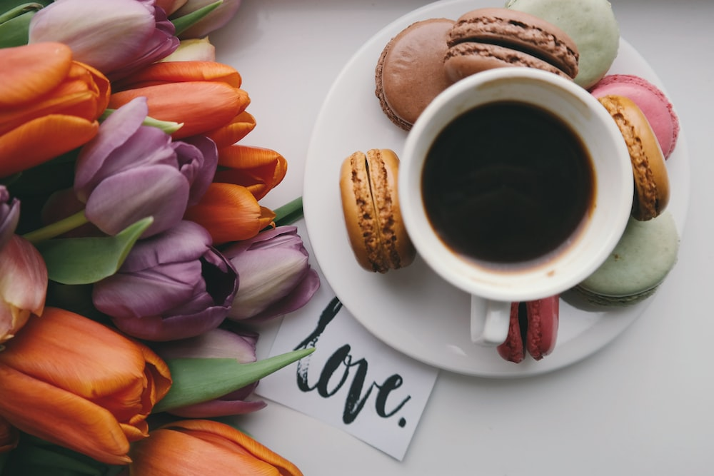 A black coffee in a small cup on top of a plate, surrounded by flowers and snacks.