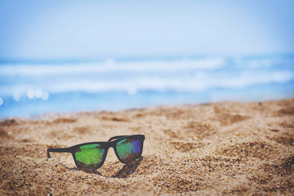 Colorful reflections in a pair of sunglasses left on a golden beach