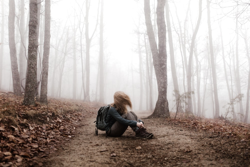 A long-haired woman sitting on a dirt path in a misty forest