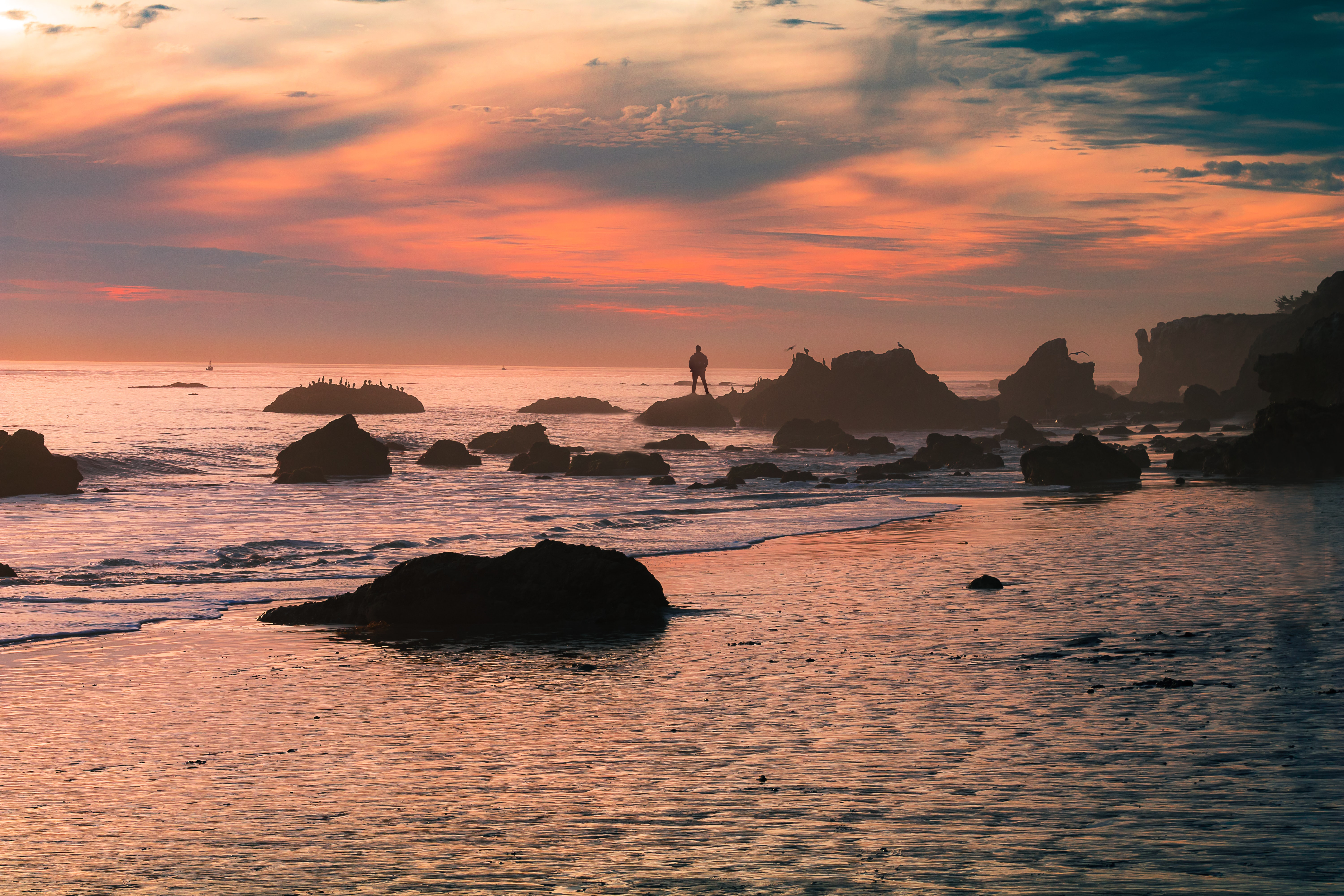 A pastel sunset covers the shores of El Matador State Beach as a man stands over the rocks