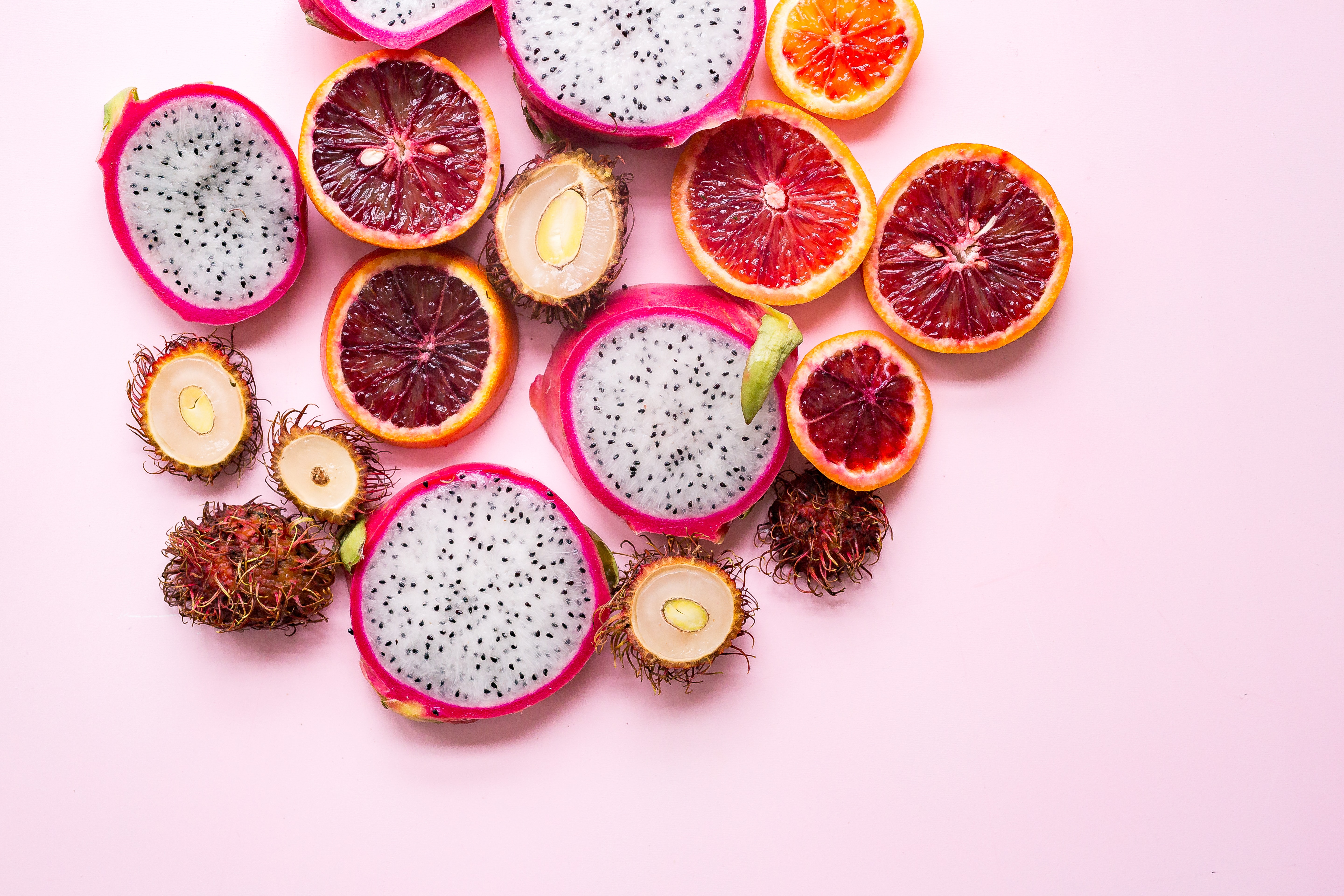 Slices of blood oranges, dragon fruit, and tropical fruit