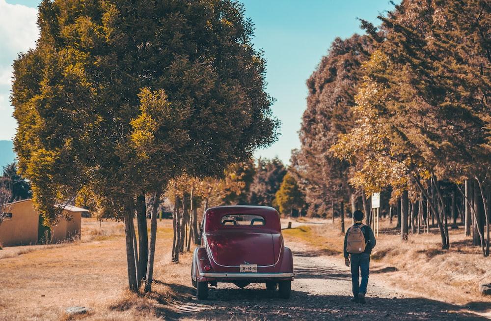 man walking beside red car