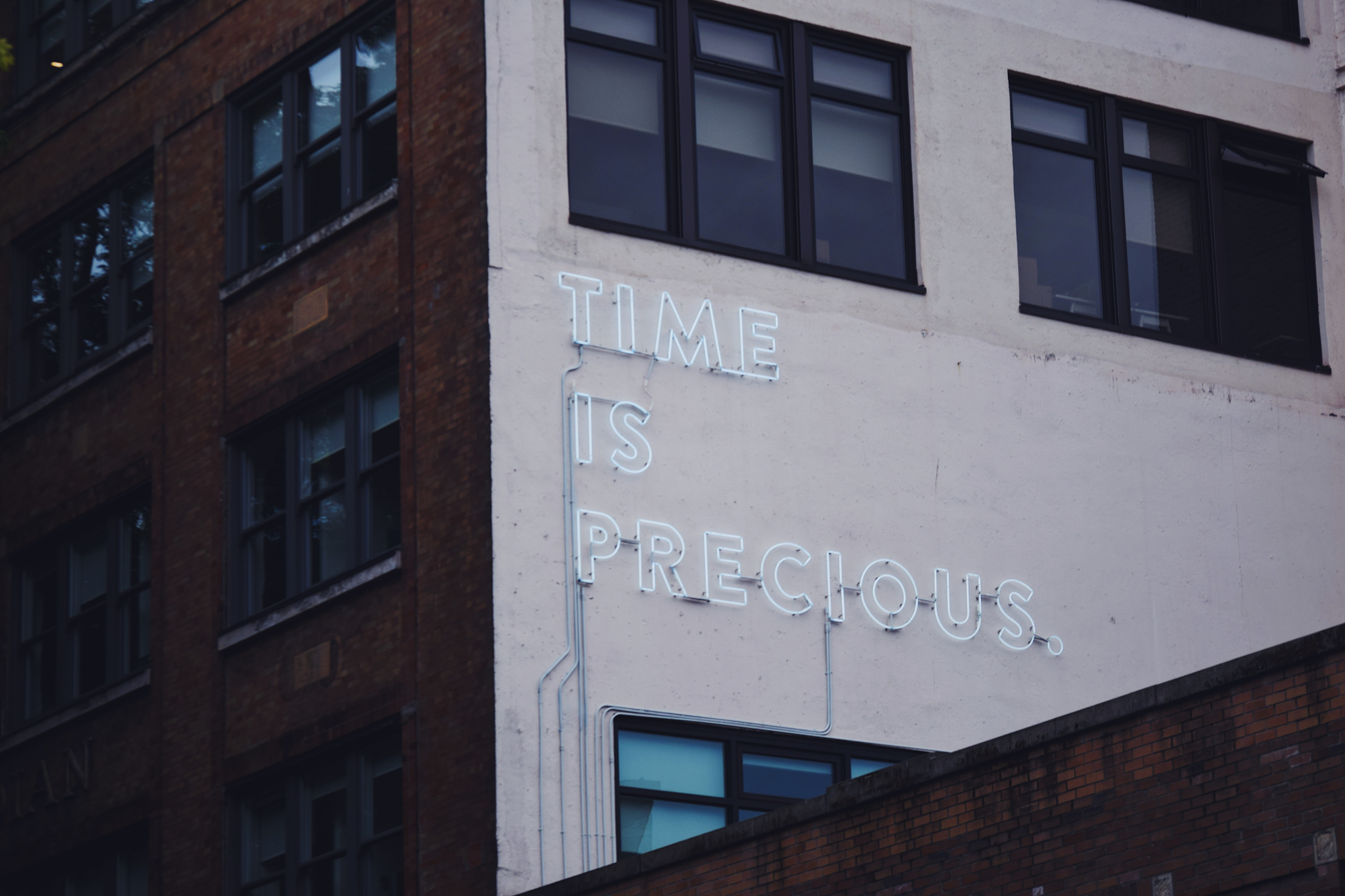 "A white ""time is precious"" neon on a building facade"