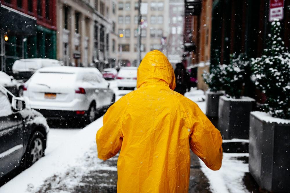 person wearing yellow raincoat walking in the street