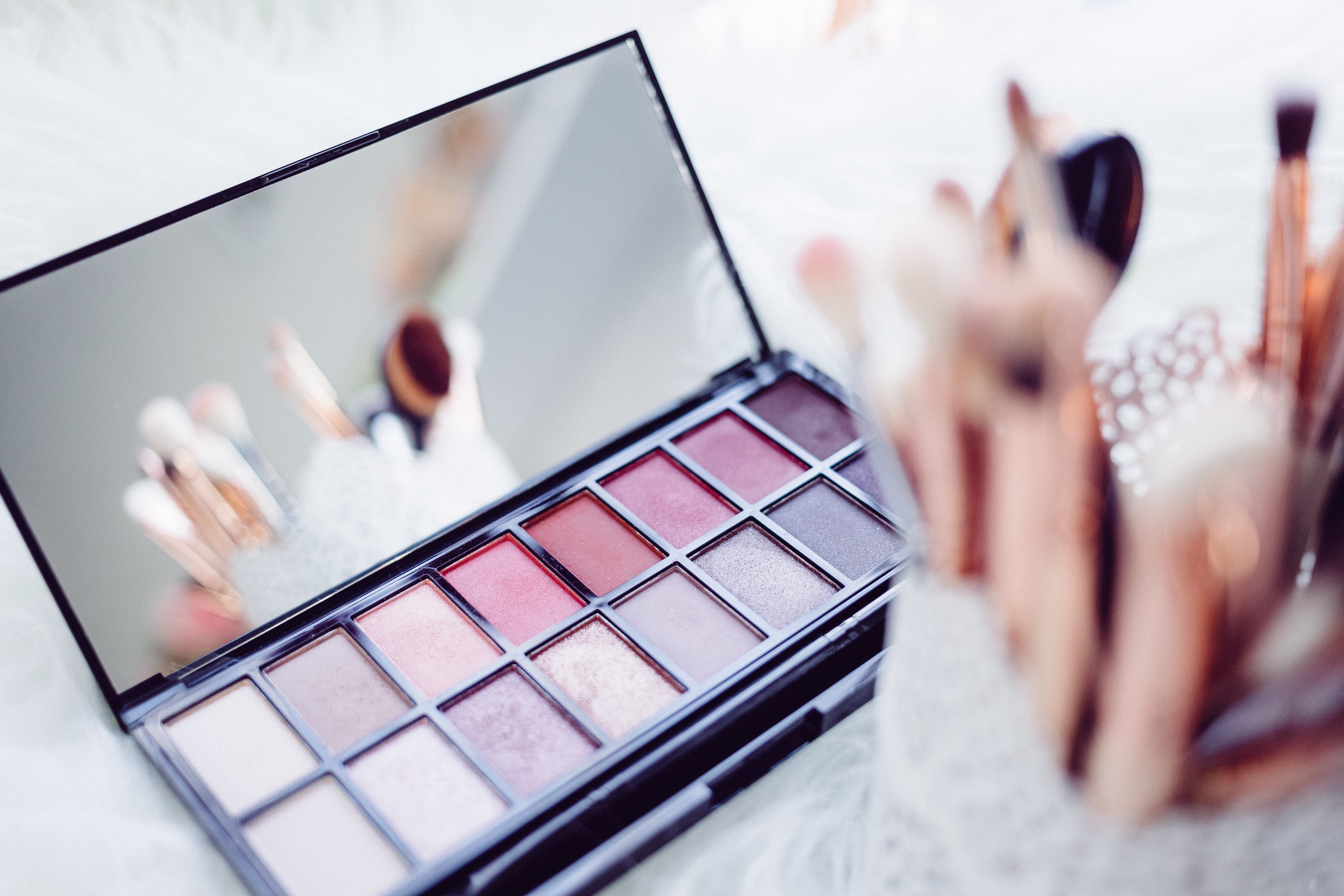 In-focus shot of a makeup palette and brushes.