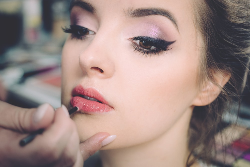 woman getting lips applied with lipstick