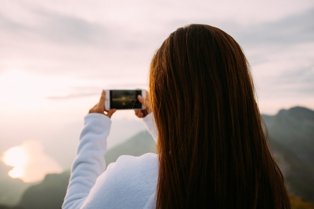 person holding smartphone taking photo