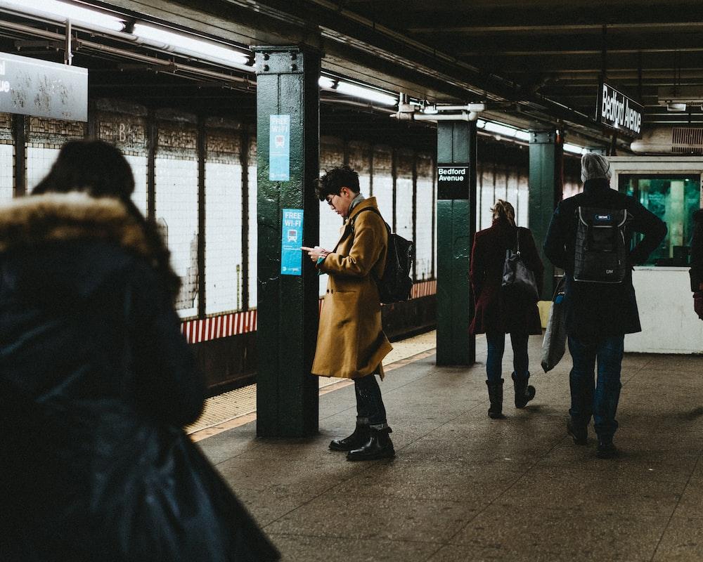 man using smartphone inside the train station