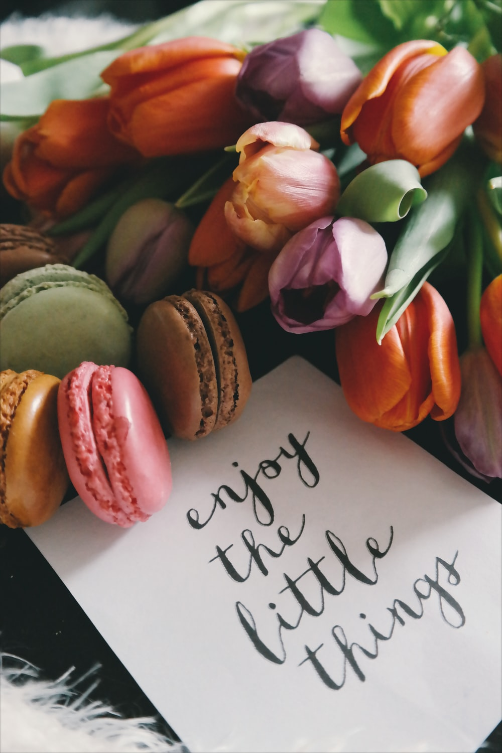 "A piece of paper next to colorful snacks that reads ""Enjoy the little things."""