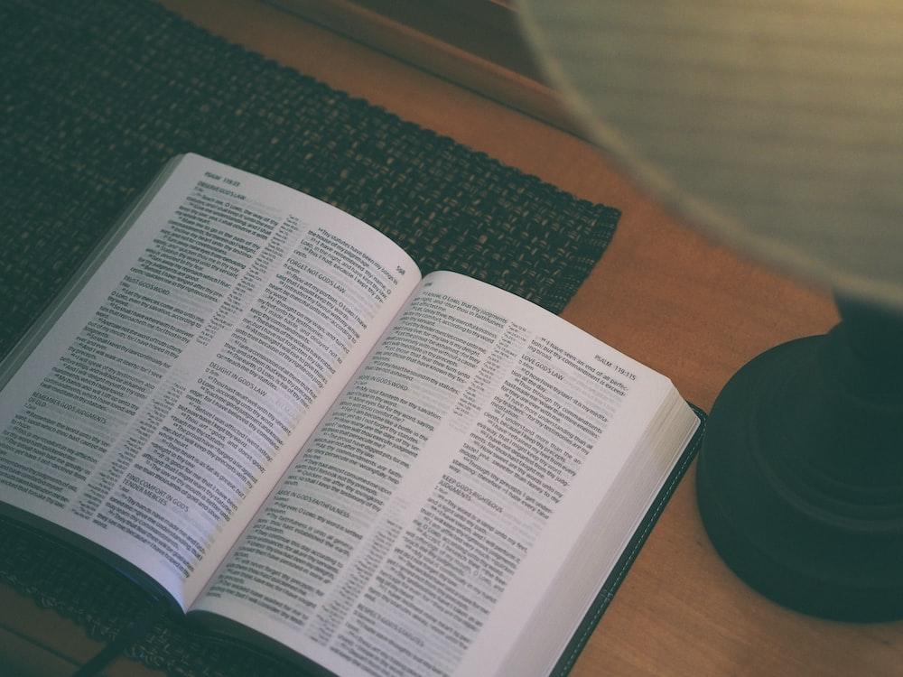 white book beside black table lamp