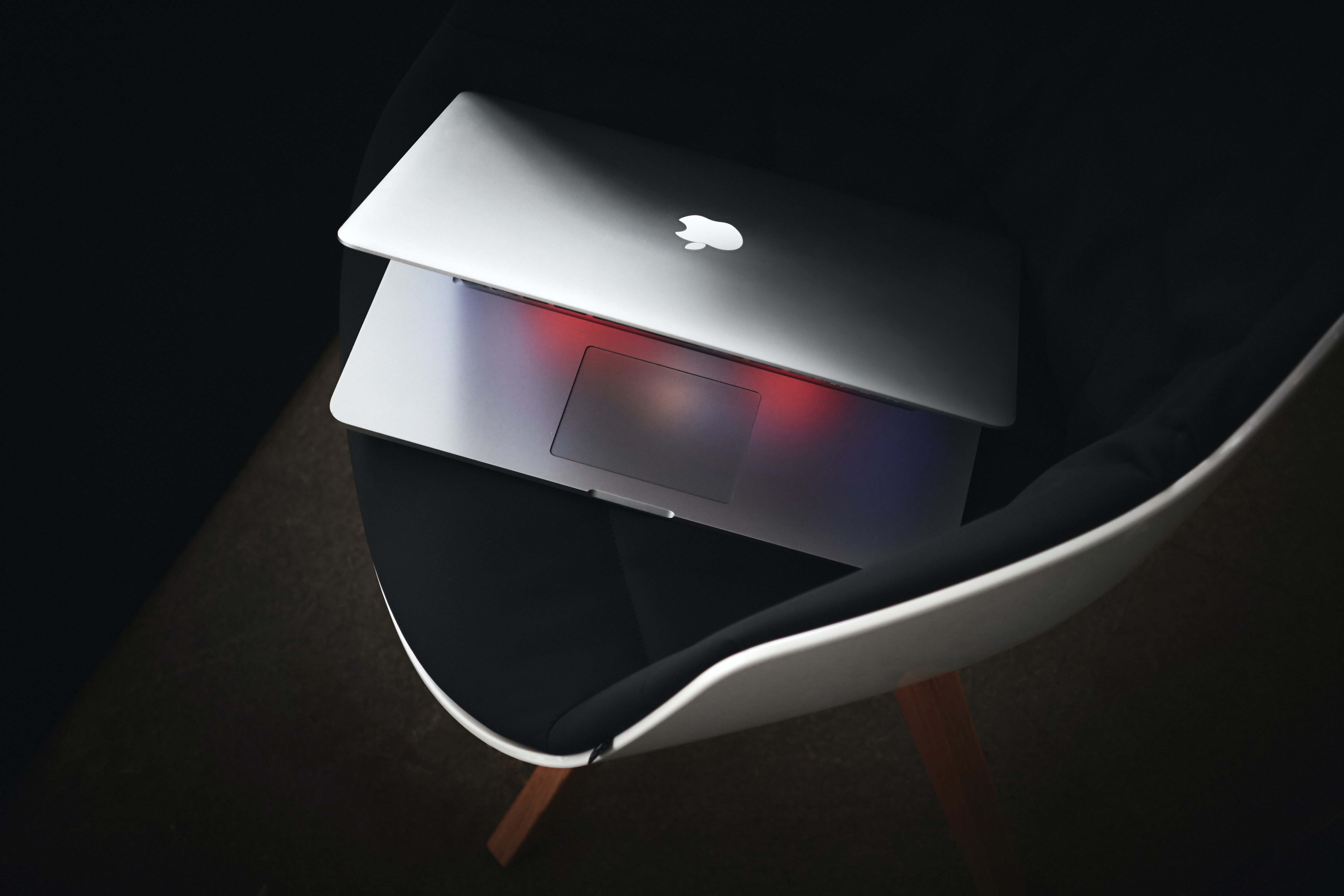Macbook sitting half- open on a black chair in a black room