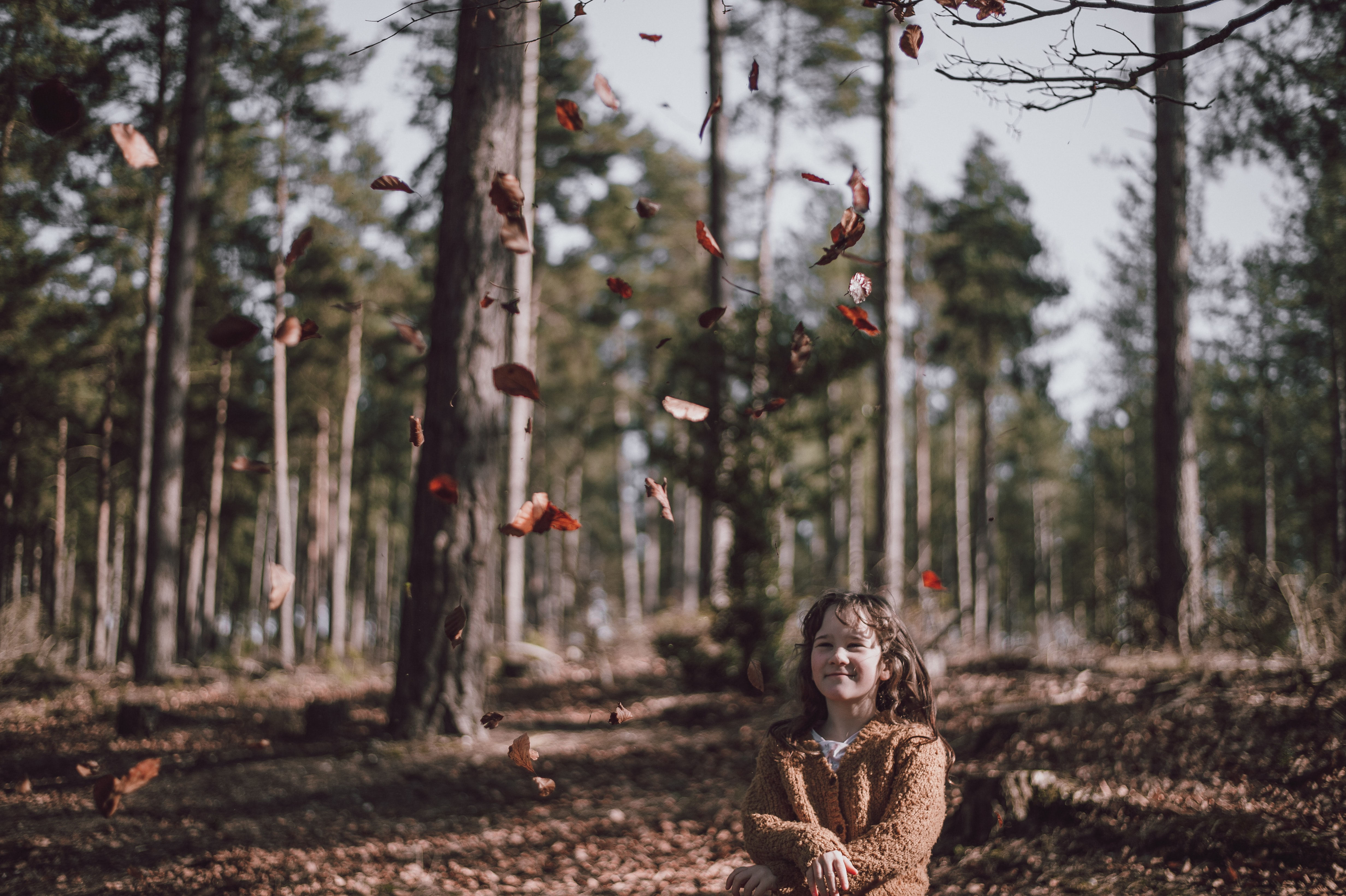 A girl throwing autumn leaves up in the air