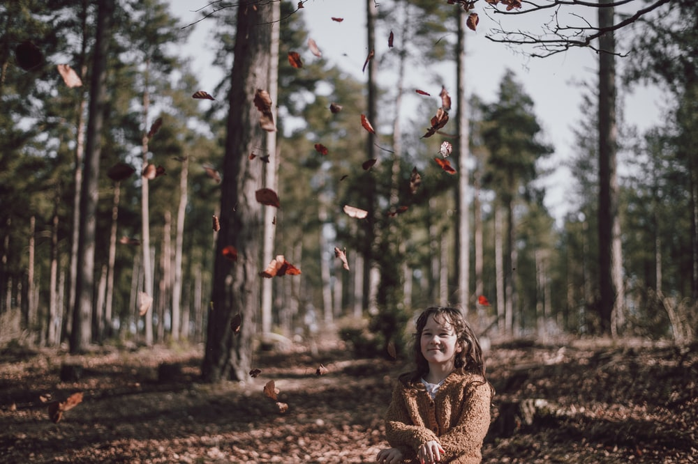 girl wearing brown jacket looking at leaves flying at daytime