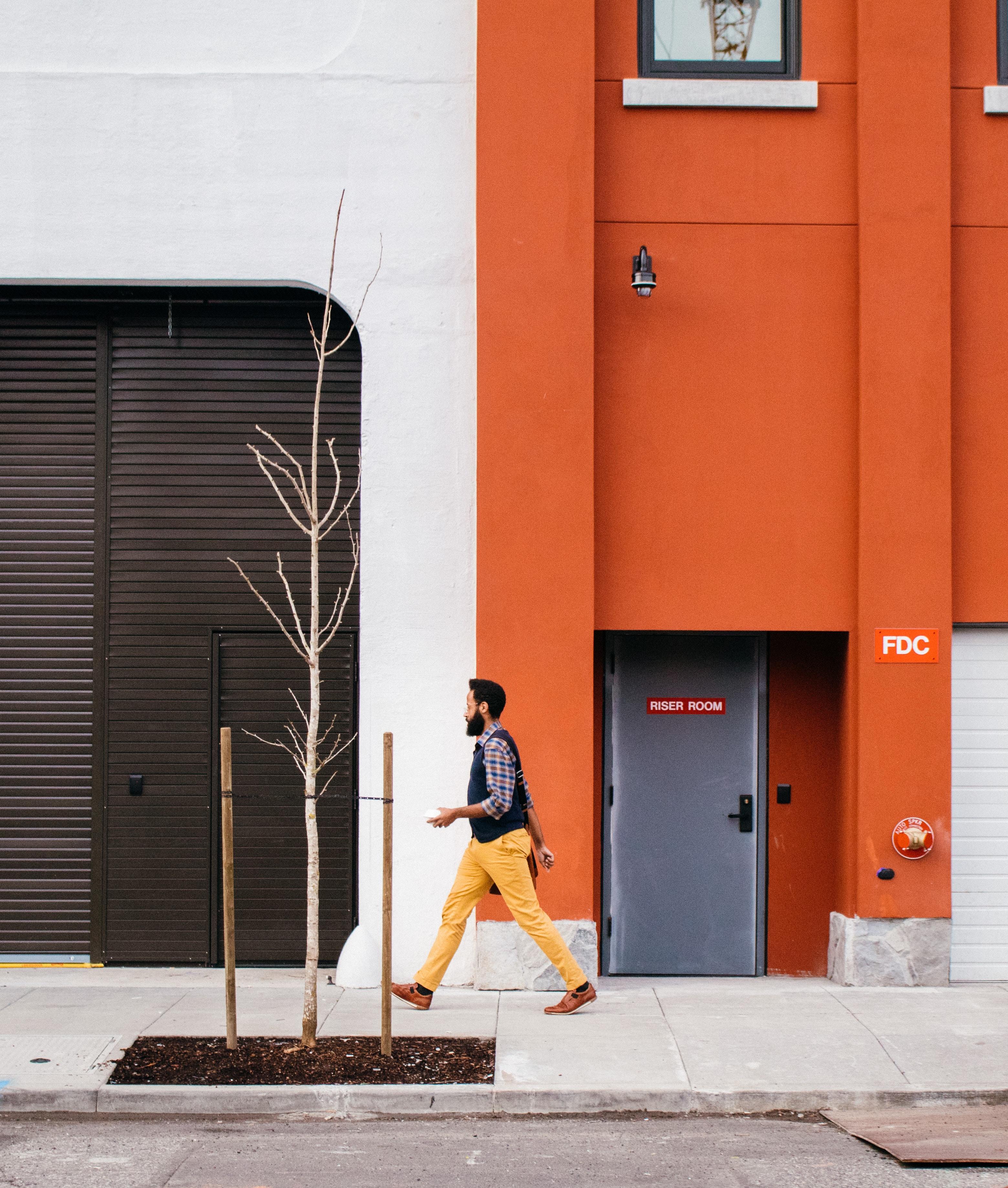 A bearded man in a vest walking on a sidewalk along an orange-painted building