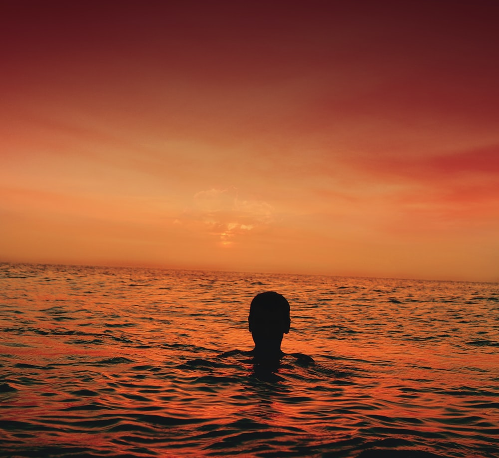 silhouette of person in ocean during sunset