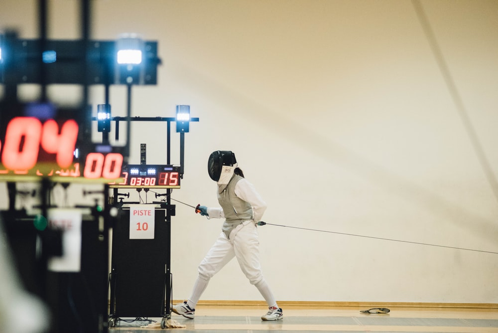 fencer standing near white painted wall
