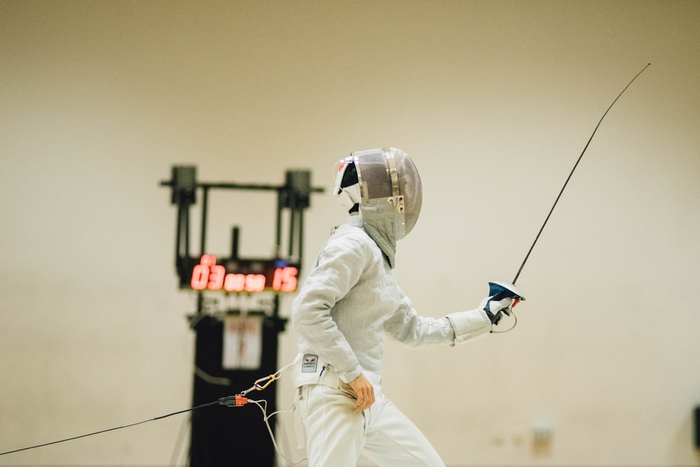 man wearing white coveralls holding fencing sword