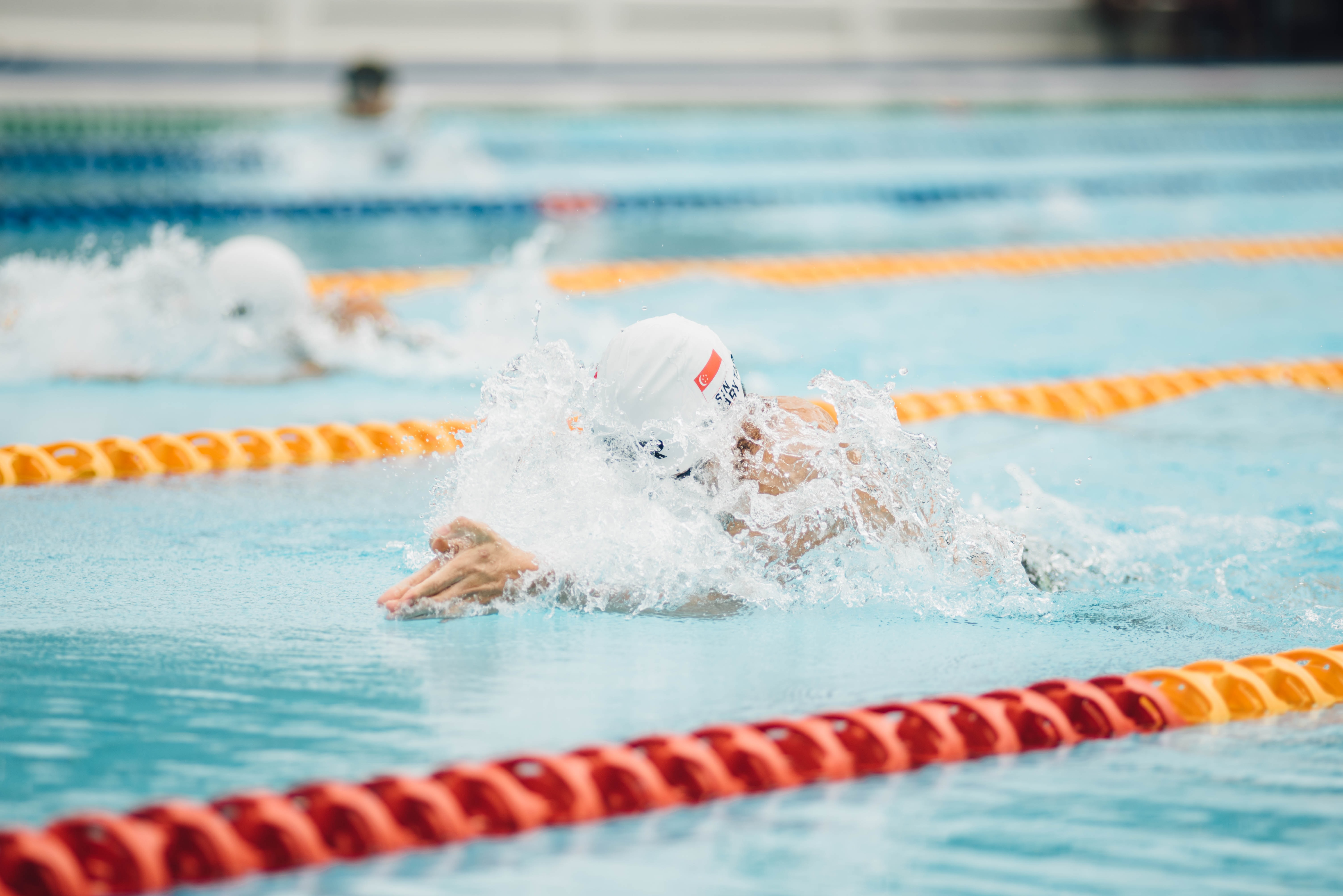 A person lane swimming in a pool, wearing a cap