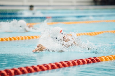 photo of person swimming swimming teams background