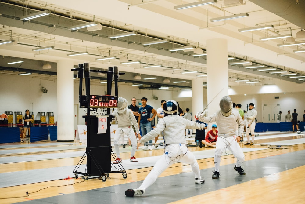 two person wearing white suit doing fencing