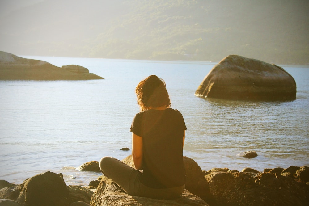 person sitting near body of water during daytime