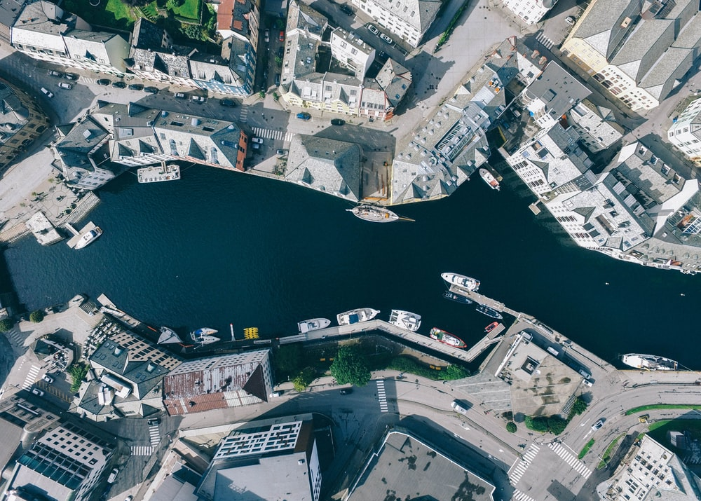 aerial photography of river in the middle of concrete buildings